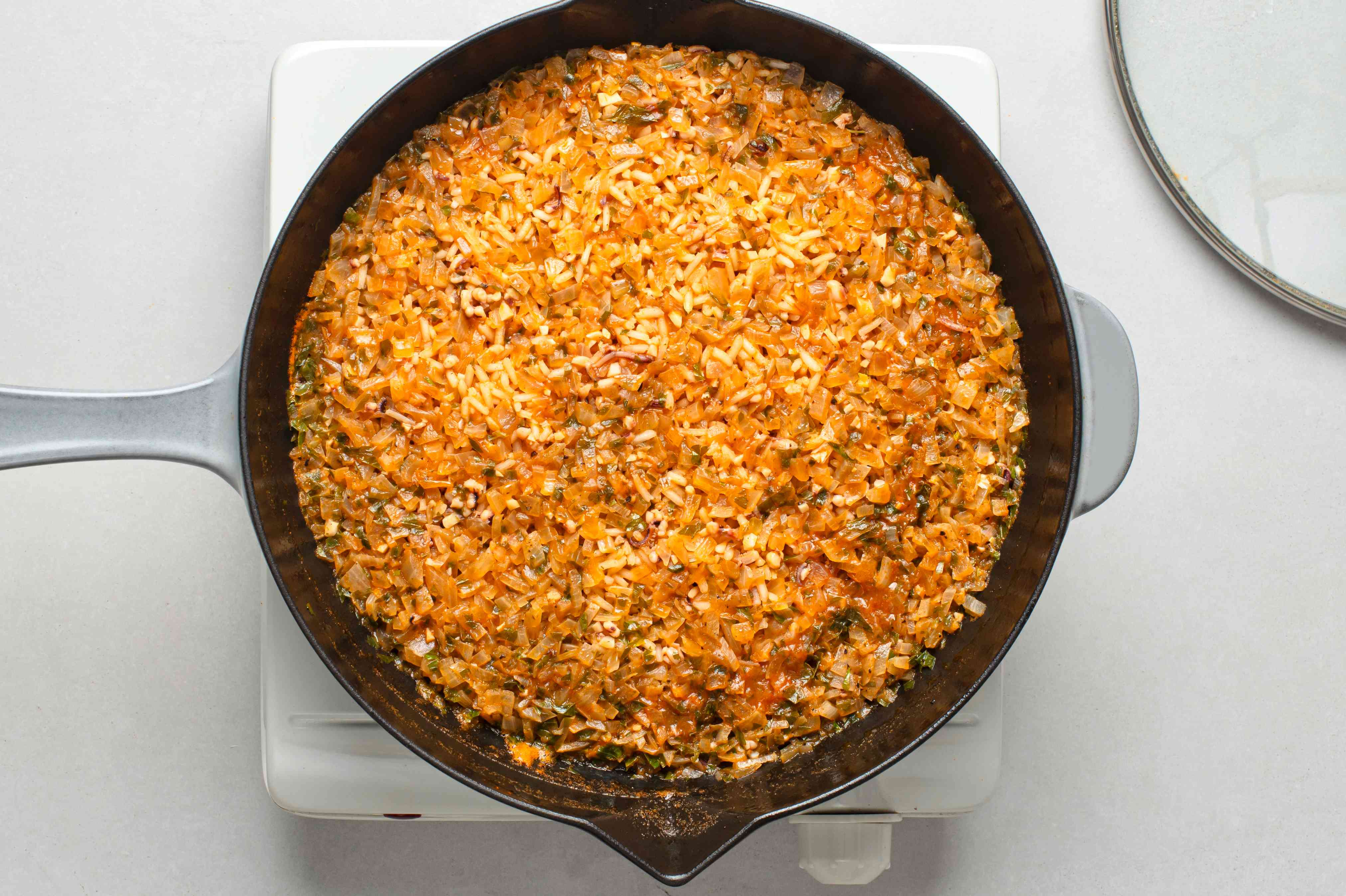 A pan of cooked rice in tomato mixture
