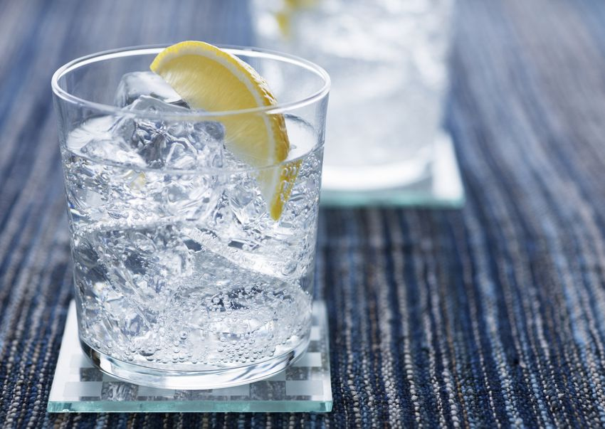 a clear alcoholic drink in a glass with lemon