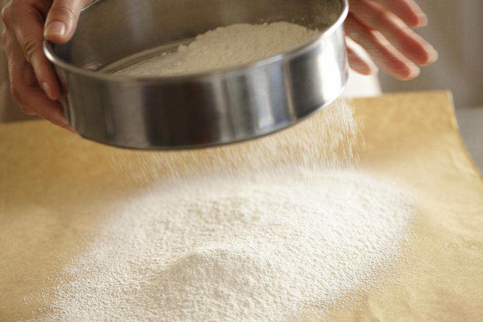 Woman sieving flour, close up
