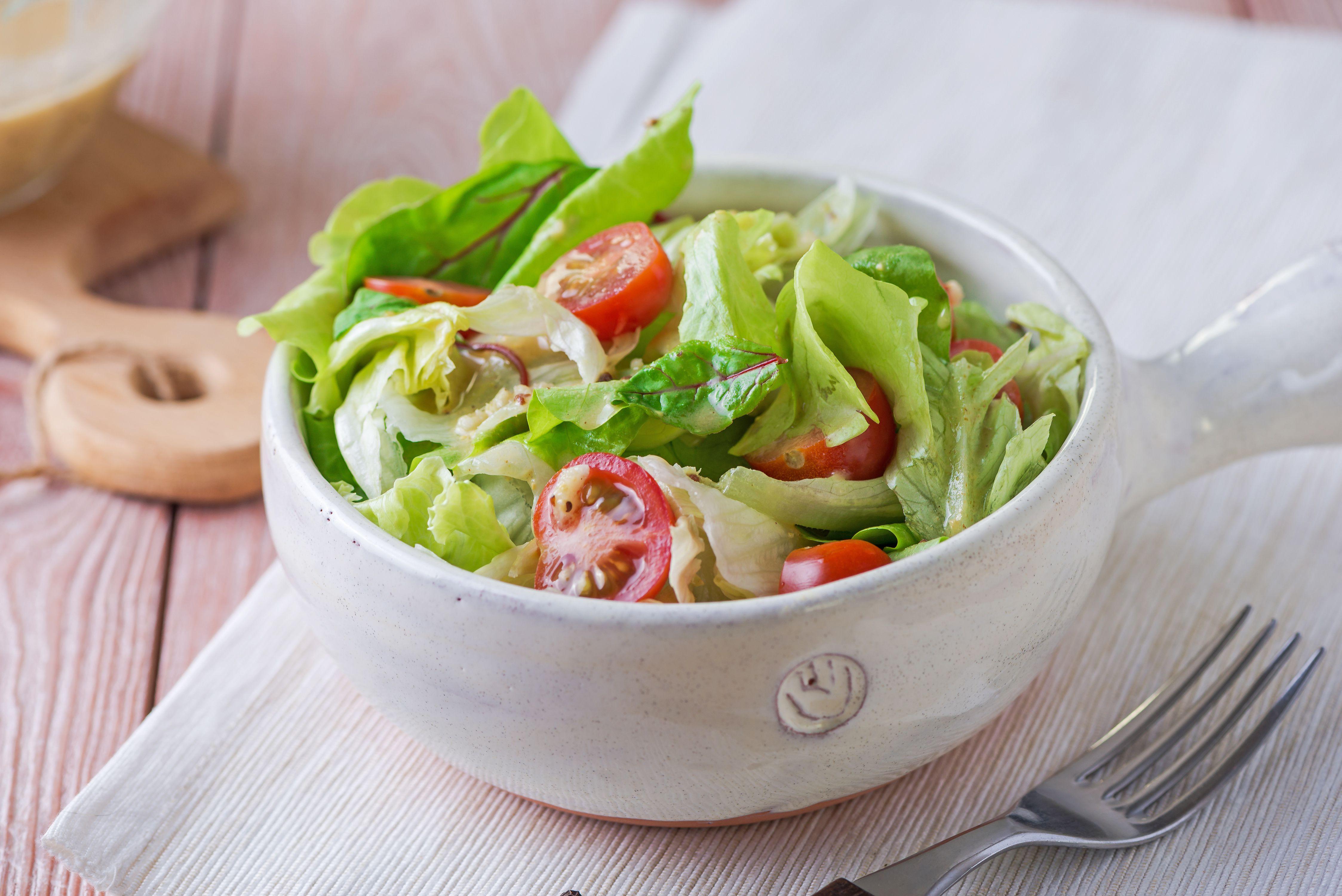 Green salad in white bowl with fat free Dijon vegan dressing