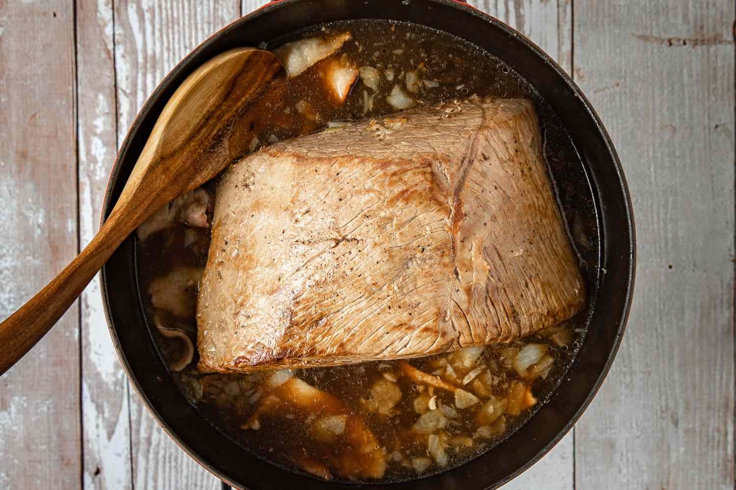 Add the onion, bacon, apple juice, beef broth and vinegar to the roast in the pan