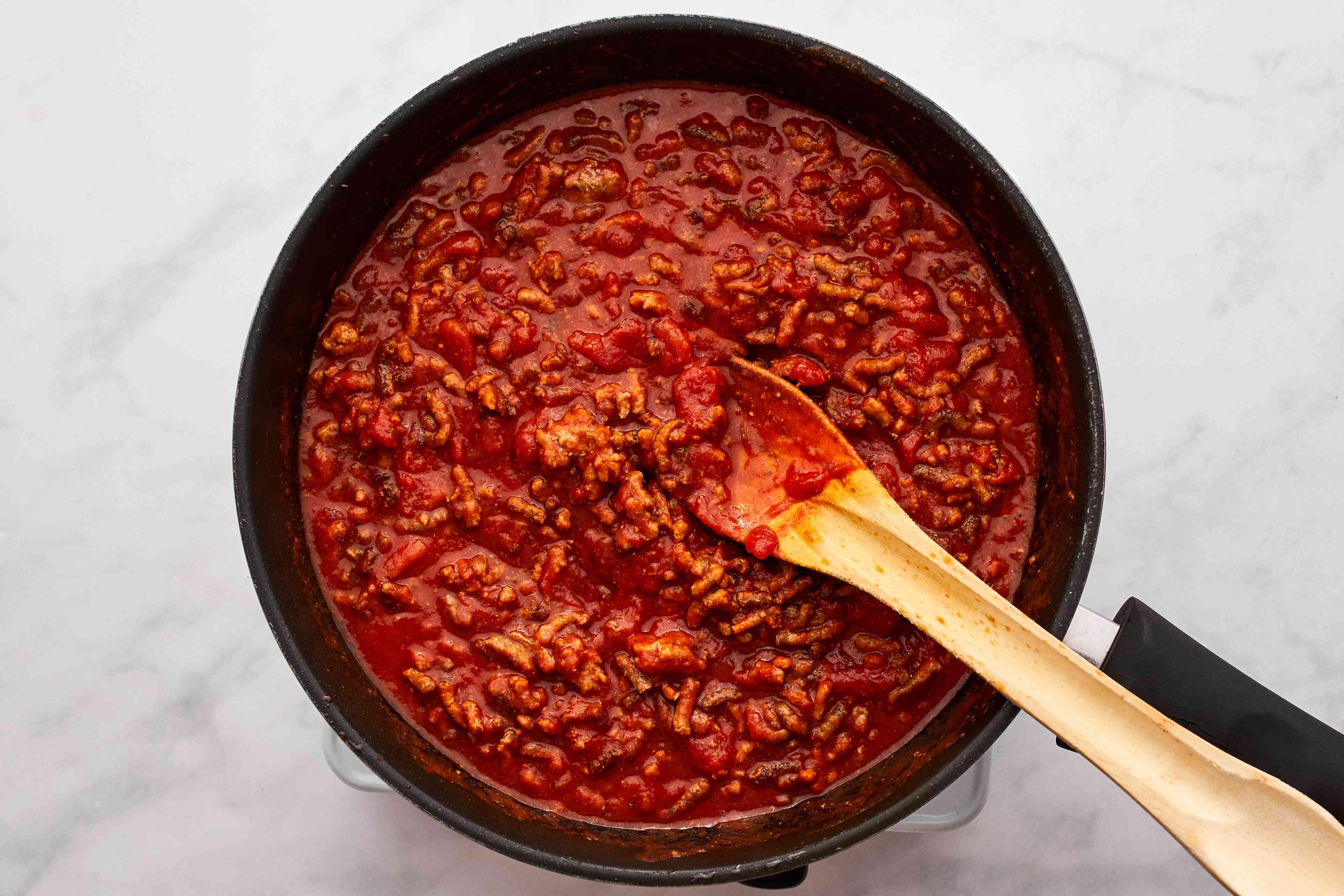 Add tomato sauce, garlic powder, 1/2 teaspoon salt, pepper, oregano, and cinnamon to the beef mixture