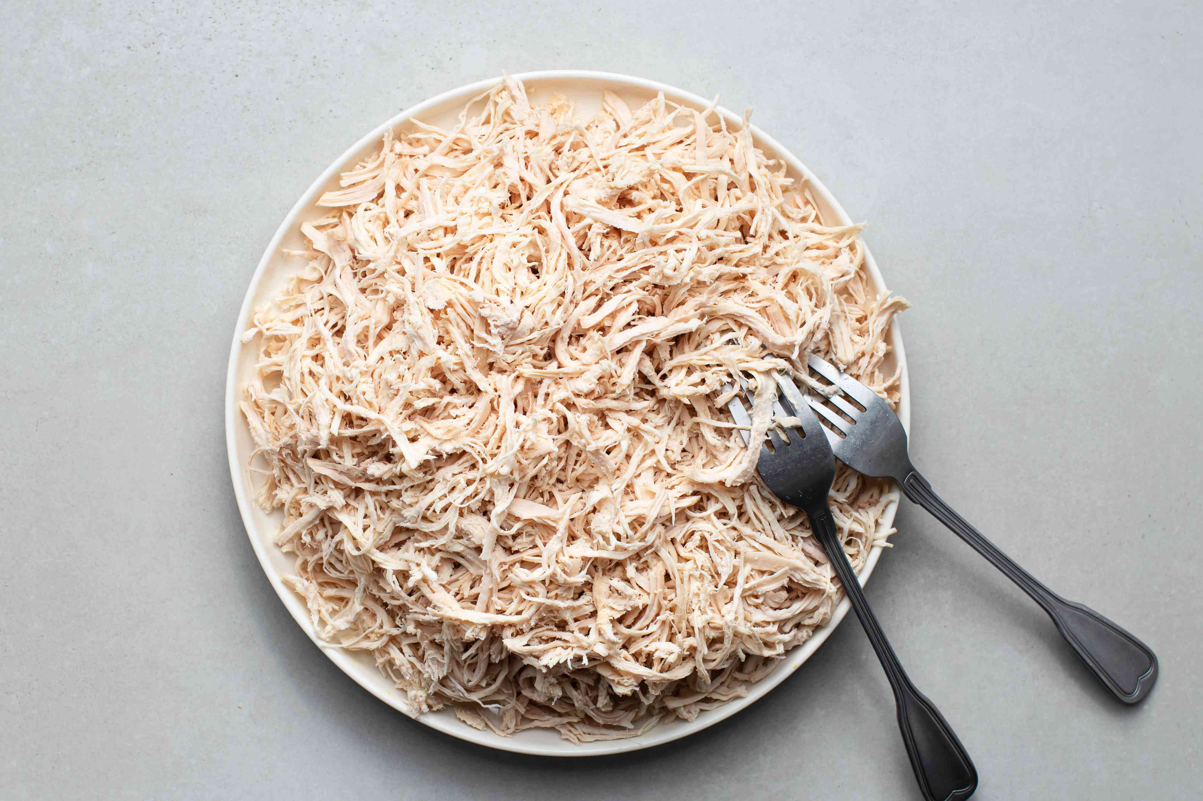 Chicken shredded with forks on a plate