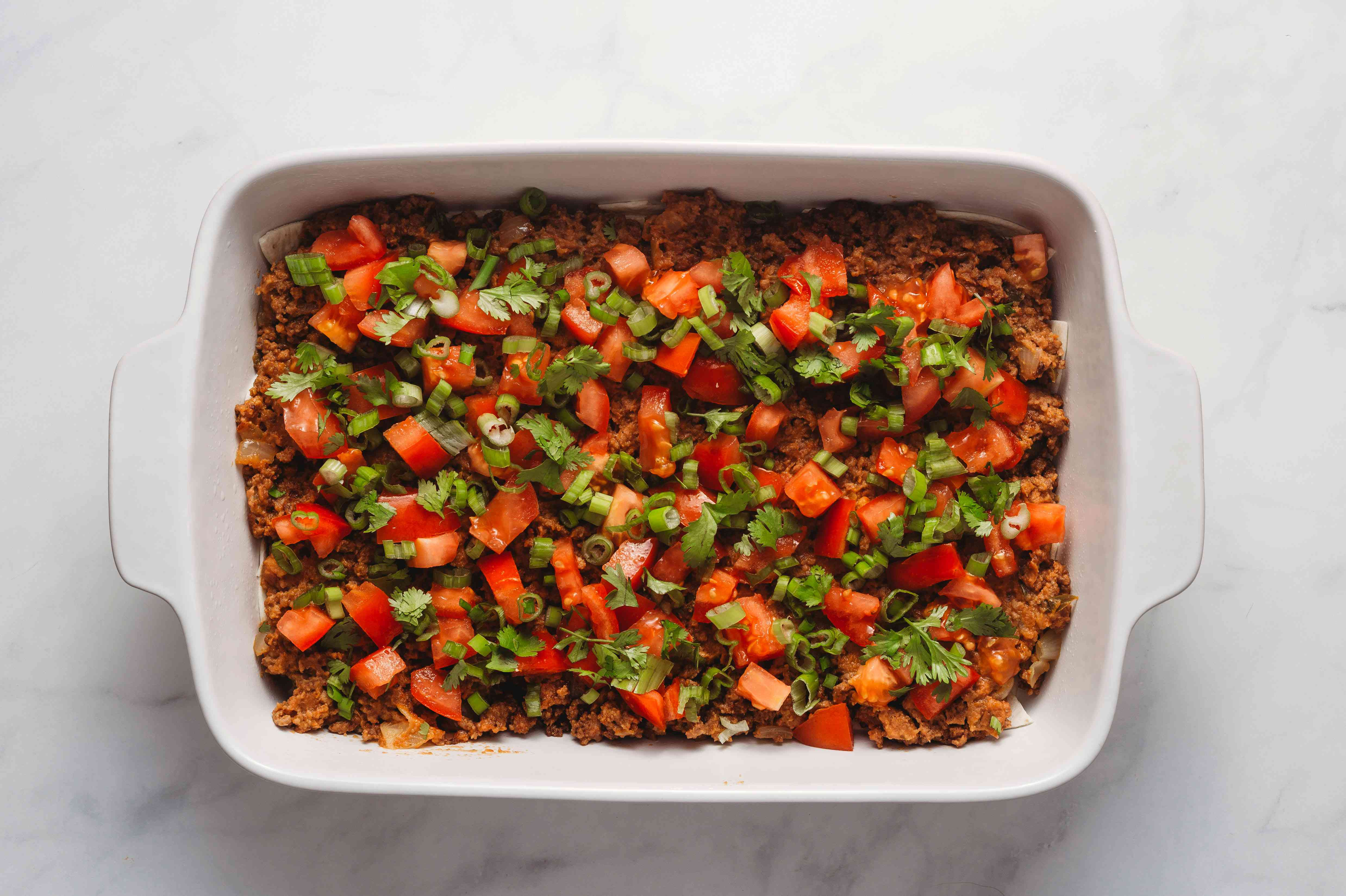 beef mixture and raw vegetables in the baking dish
