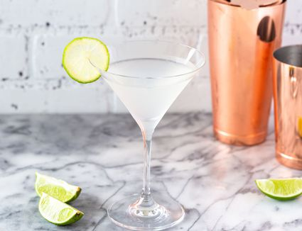 Classic daiquiri with lime garnish, lime wedges, and a copper cocktail shaker