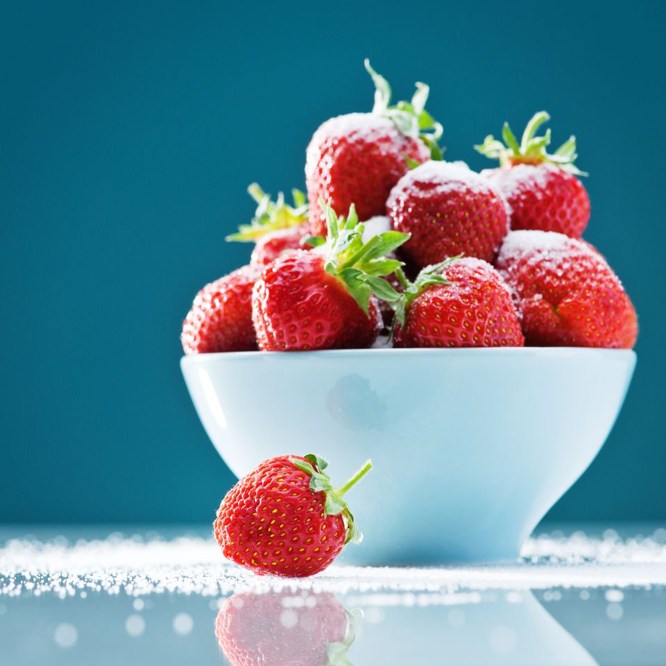 strawberries in a bowl and sugar