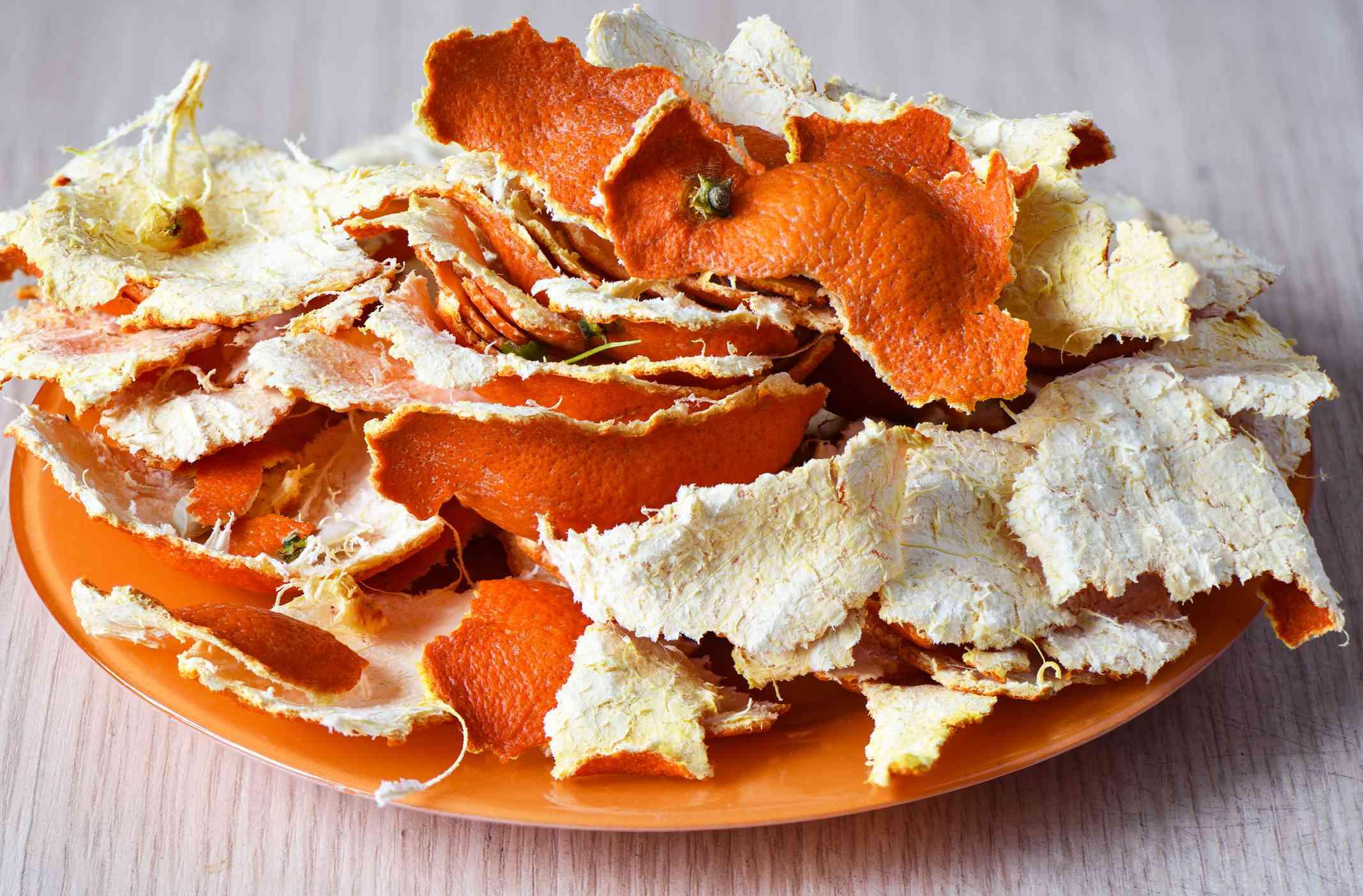 Dried tangerine peel on an orange plate.