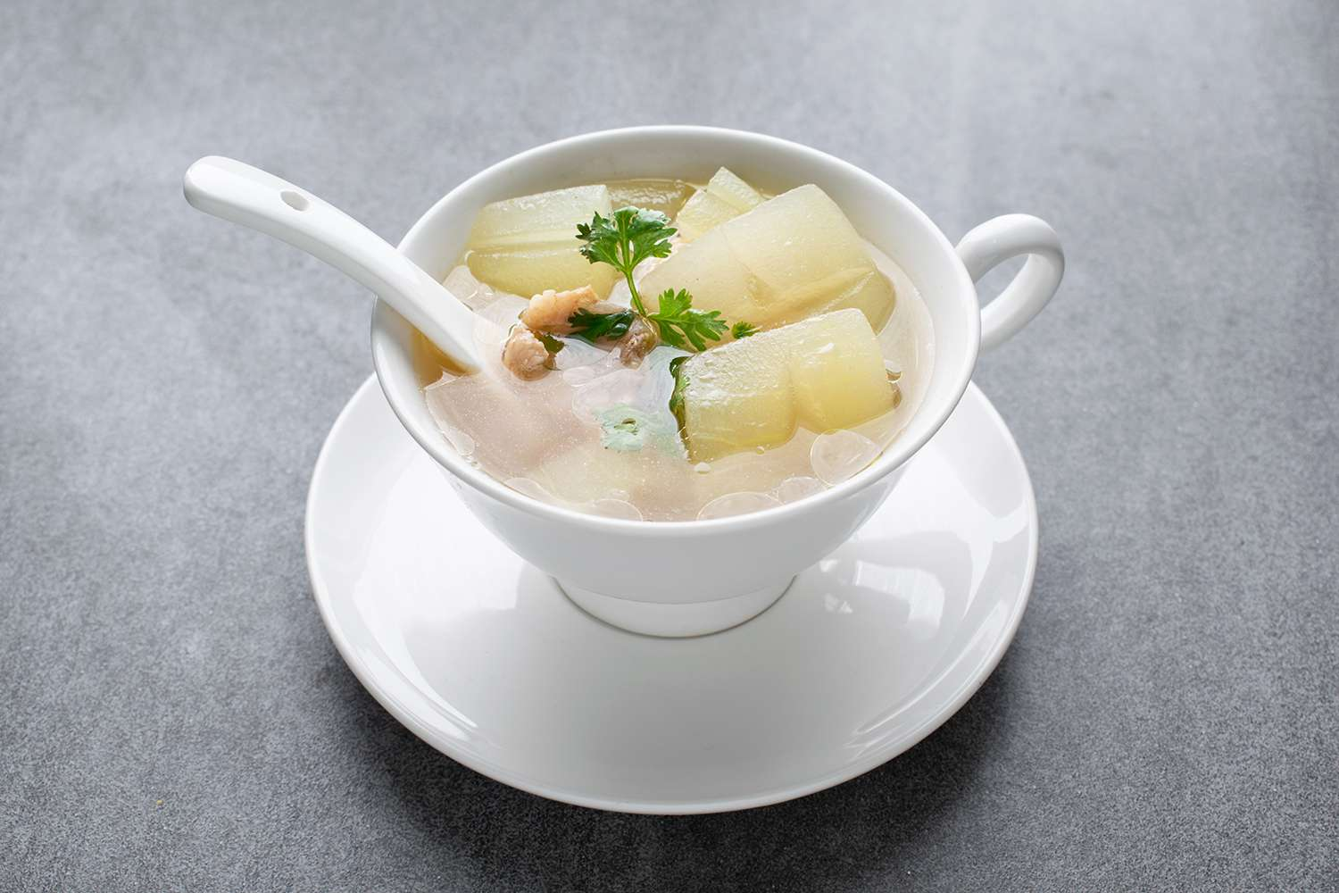Boiled winter melon soup with chicken rib in white bowl on table.