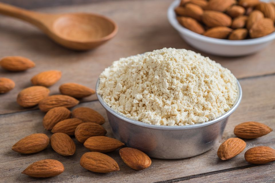 Almonds and almond meal on wooden table