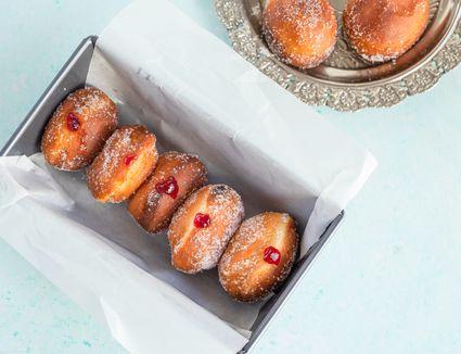 Polish pączki doughnuts recipe in waxed paper in a pan