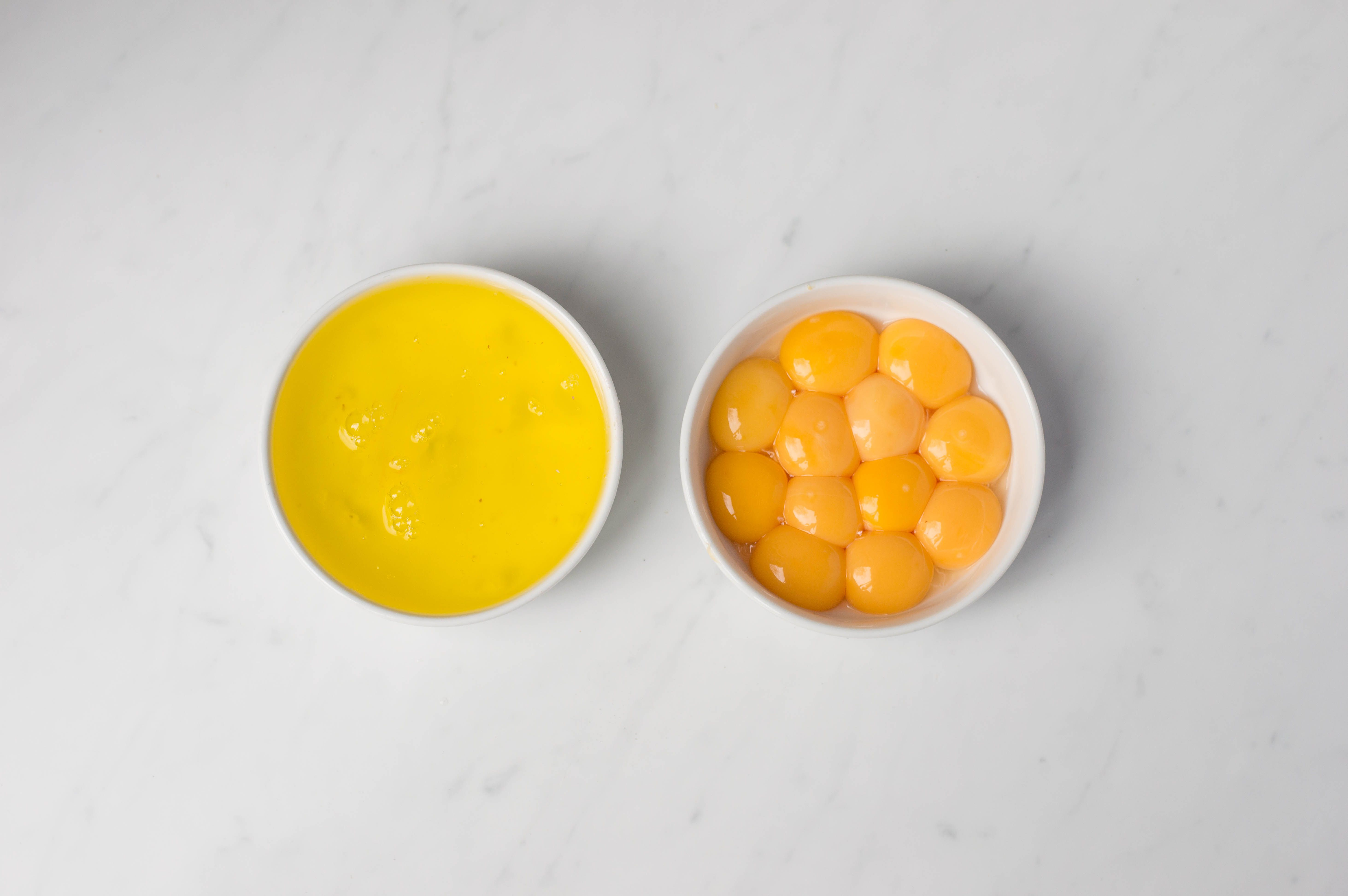 Egg yolks and egg whites in two separate bowls