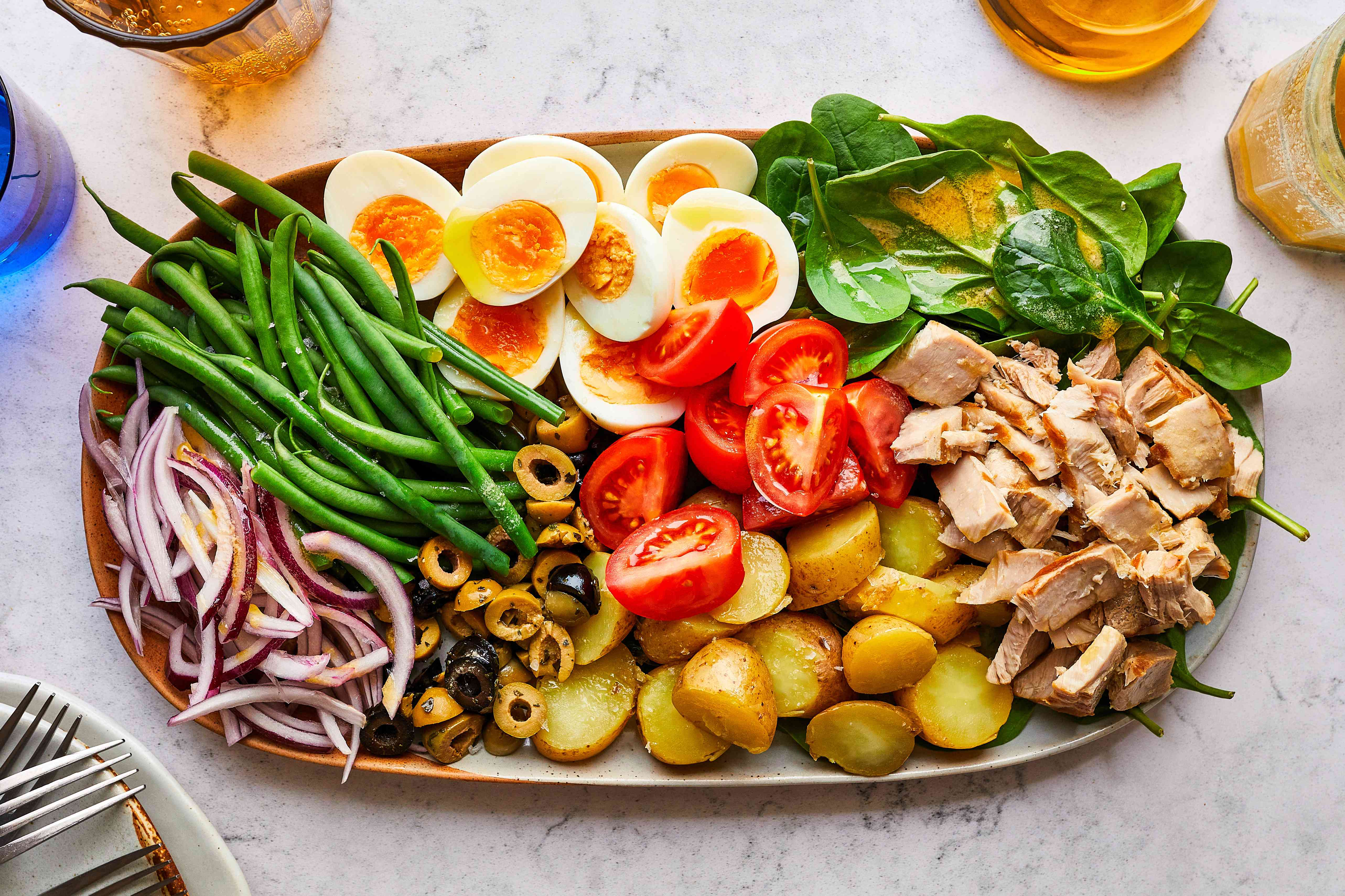 Nicoise salad with dressing on side on table