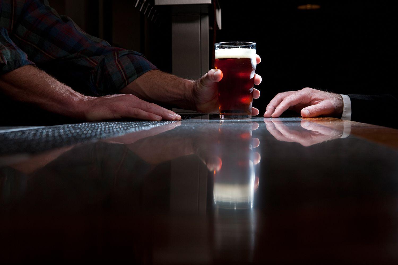 A bartender serving a beer
