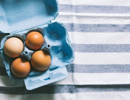 Box of eggs on striped tablecloth