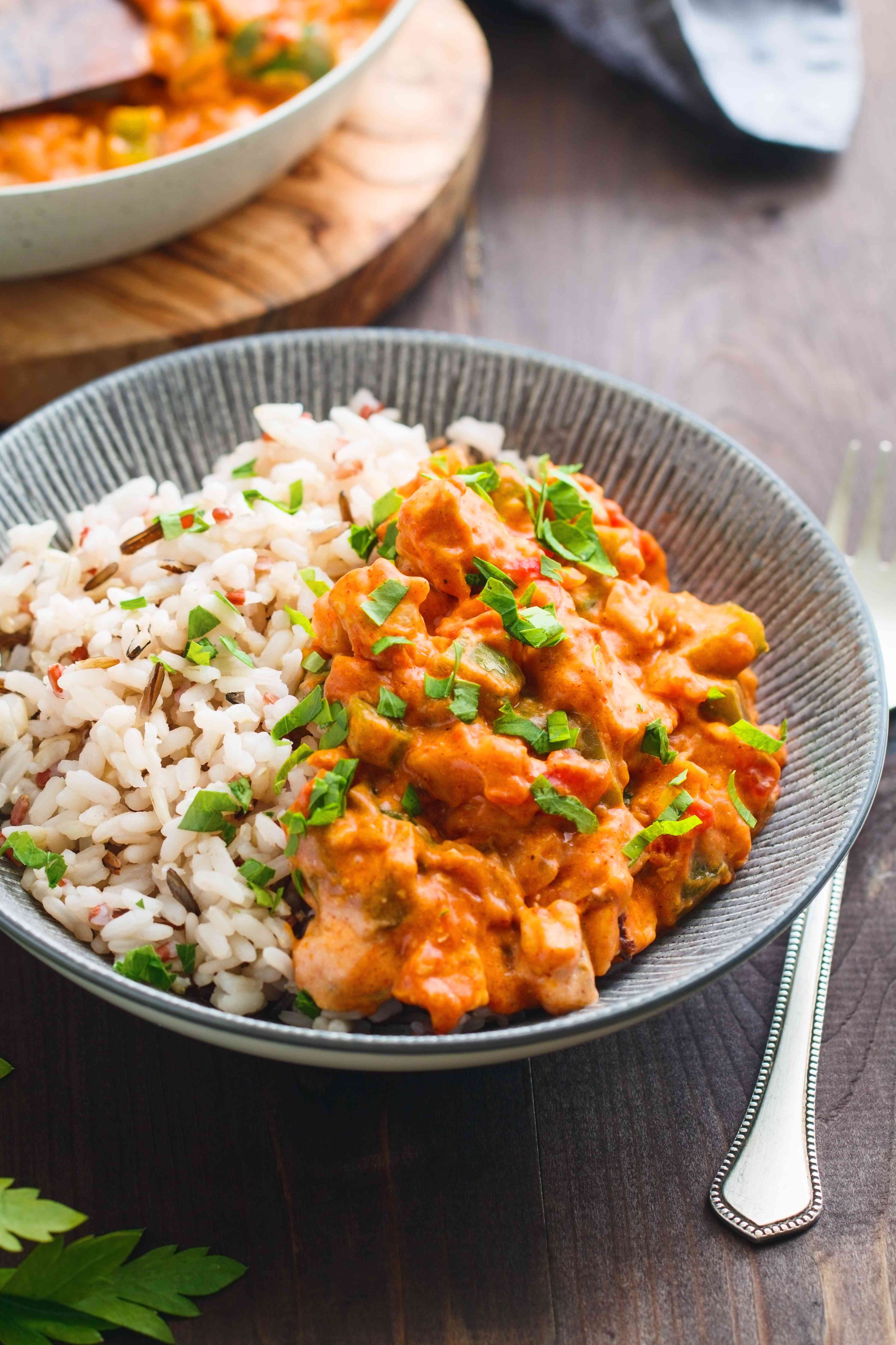 Portion Hungarian chicken paprikash in bowls with rice