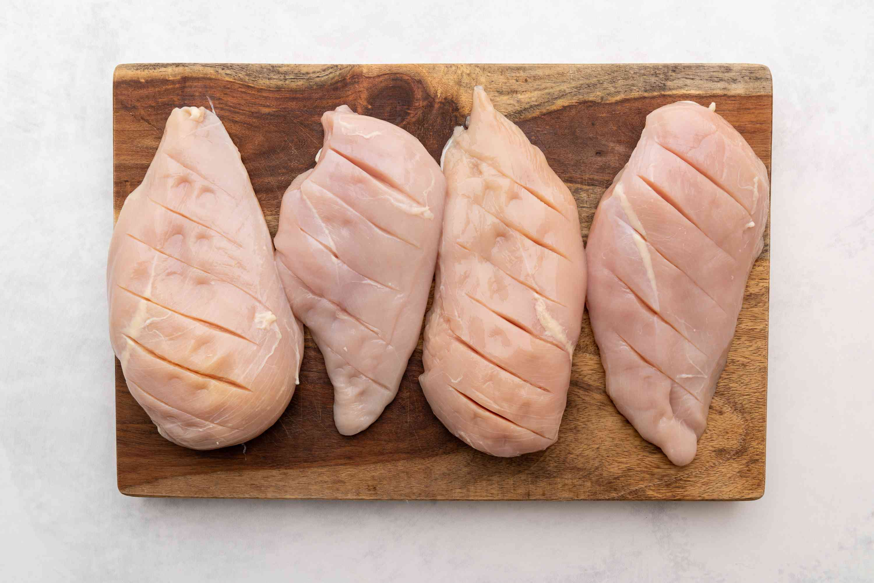 shallow diagonal slashes in the chicken pieces on the cutting board