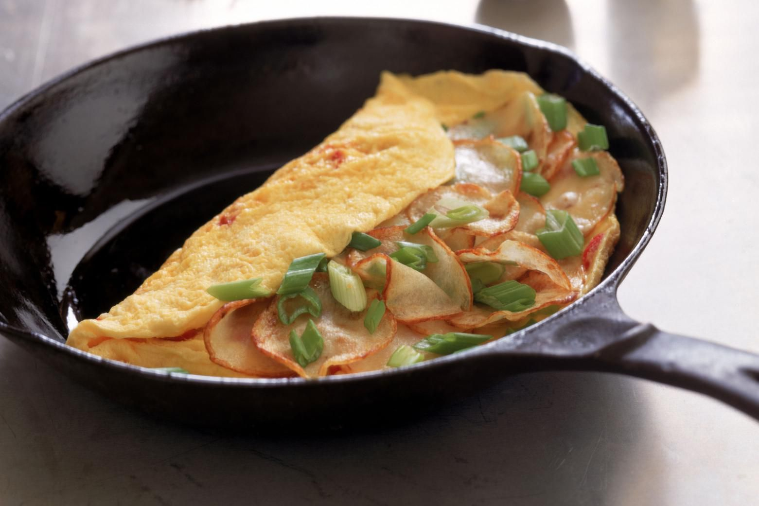 a French omelette with ham, cheese, and green onions