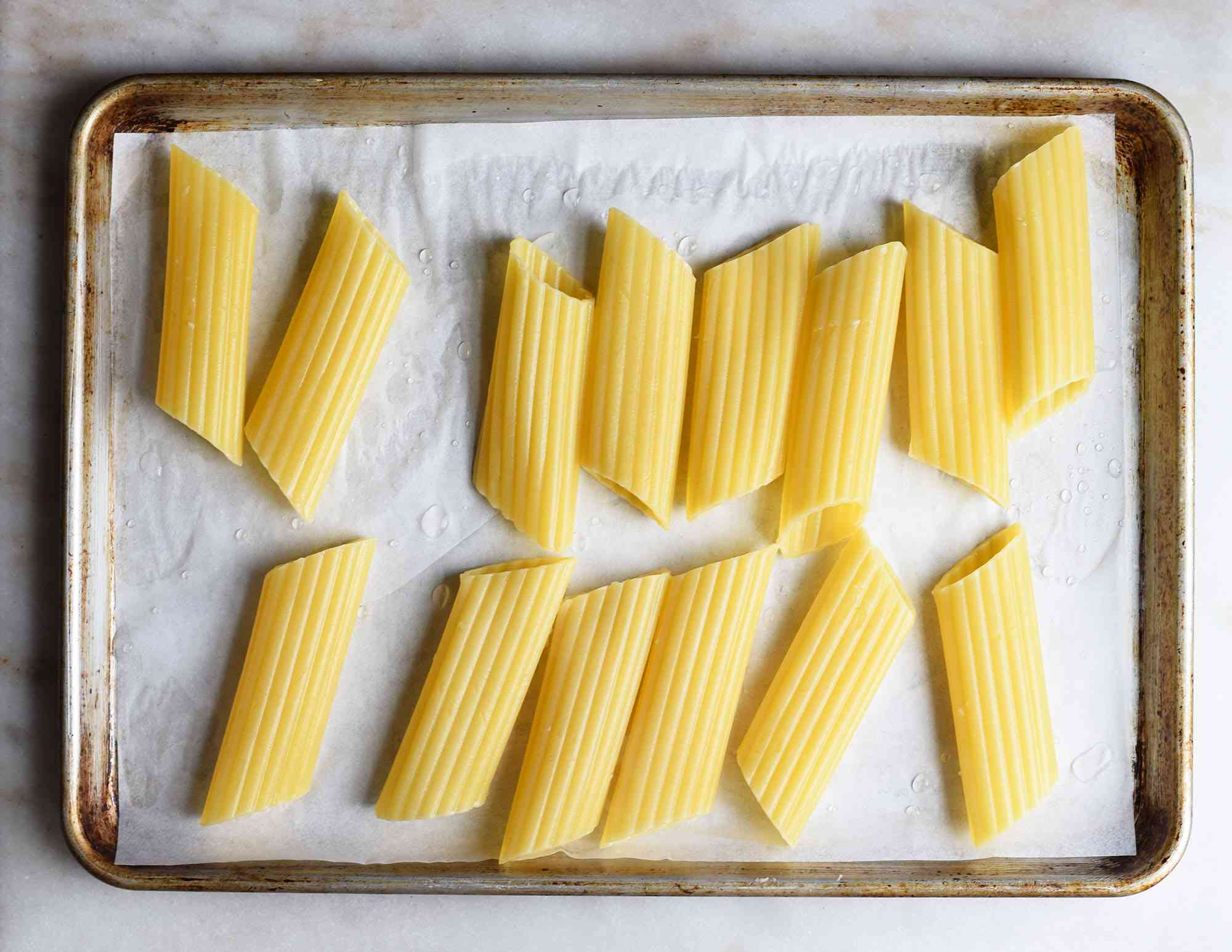 cooked manicotti noodles on a baking sheet