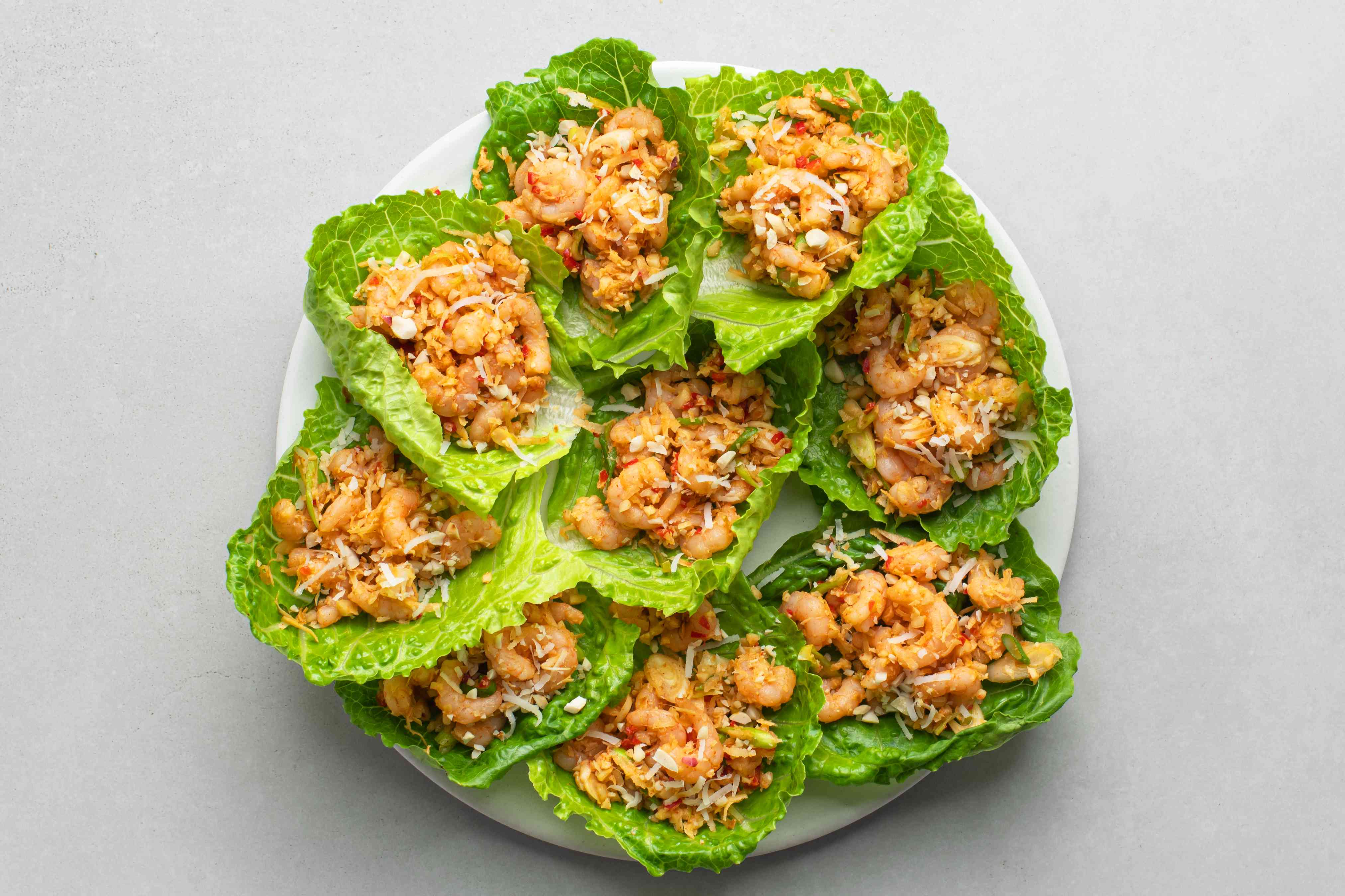 romaine lettuce leaves with shrimp mixture and coconut on top