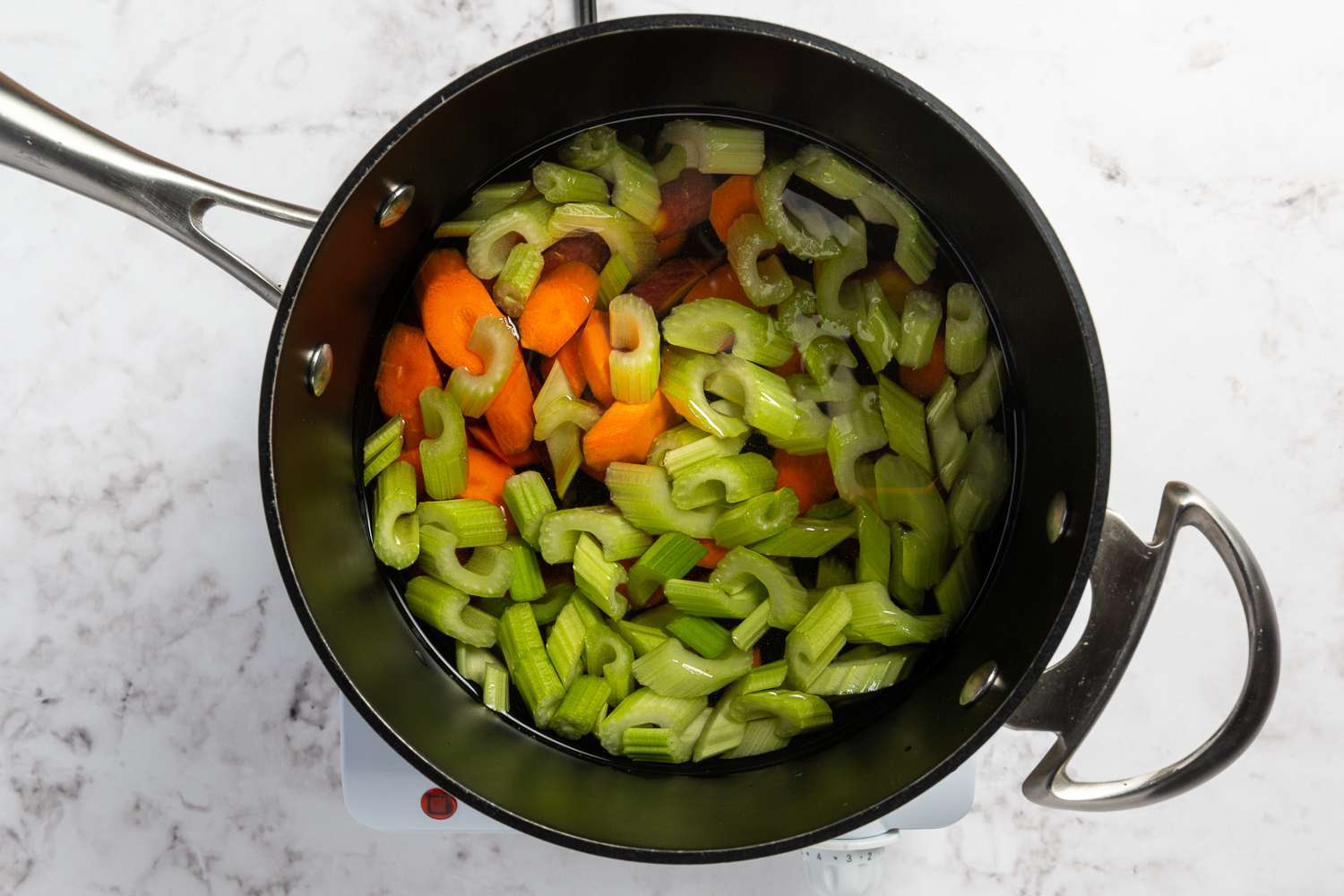 celery, onions and carrots in a saucepan