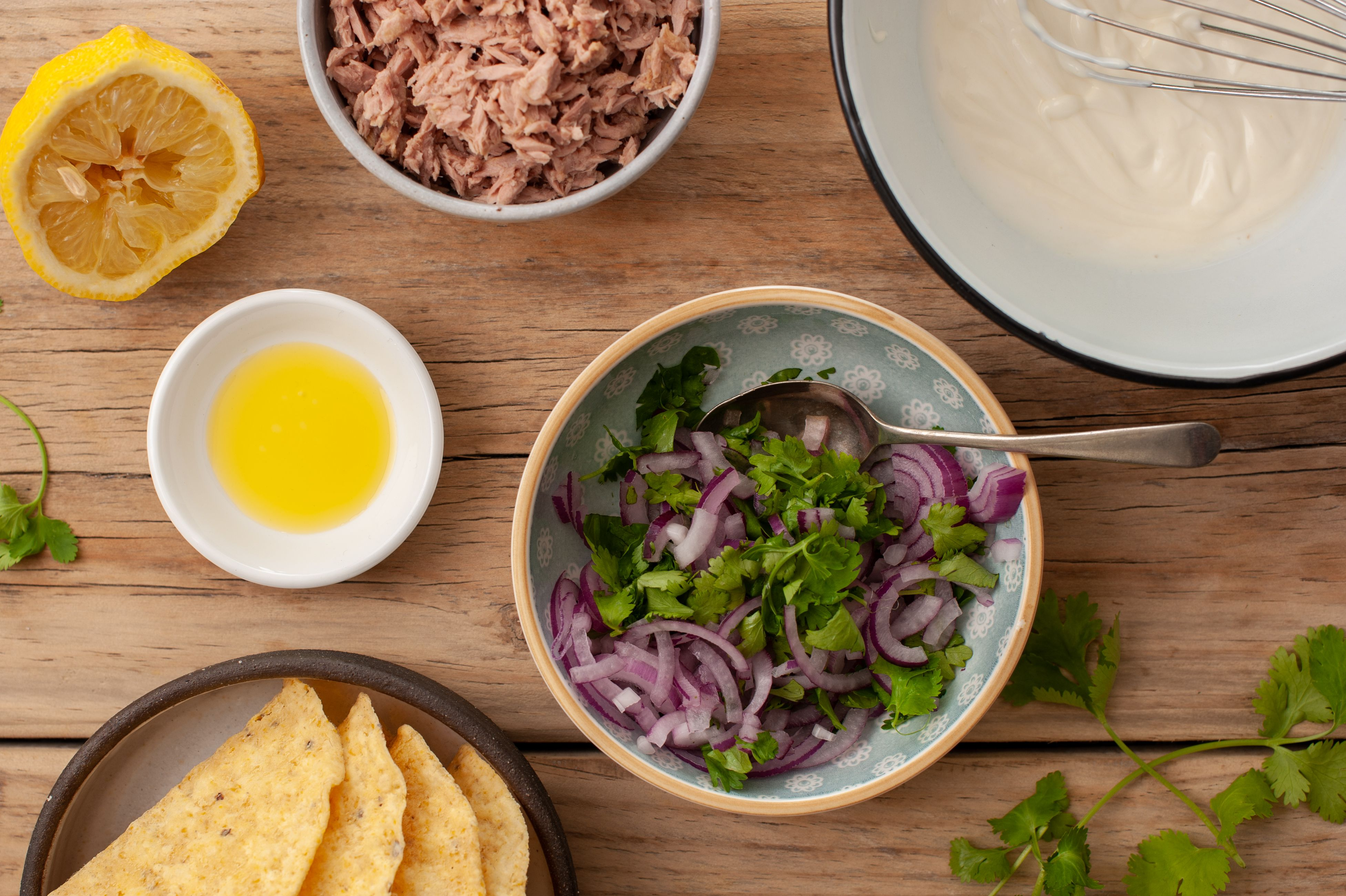 Bowl of onions and cilantro, surrounded by taco ingredients