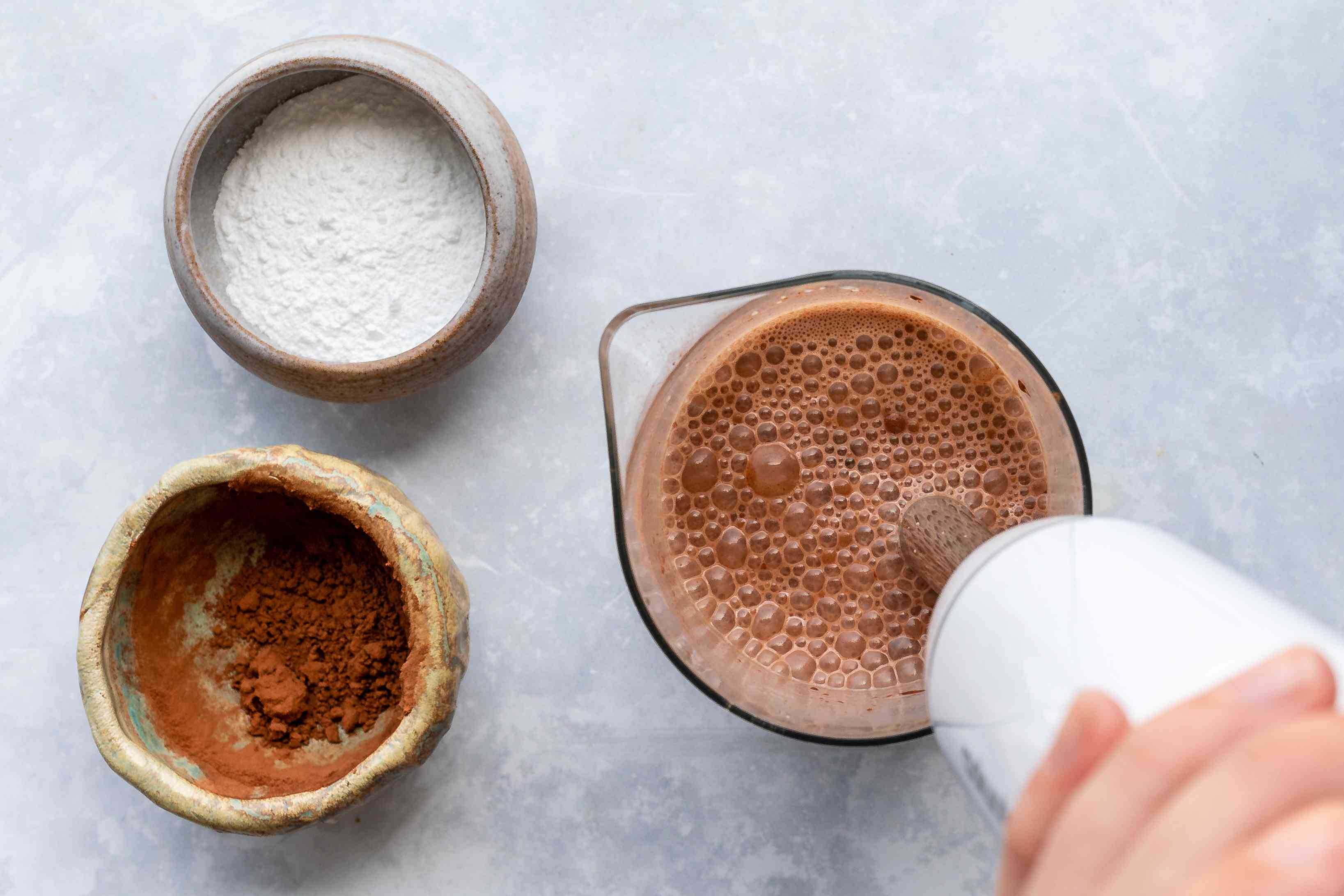 Blending milk and cocoa with an immersion blender