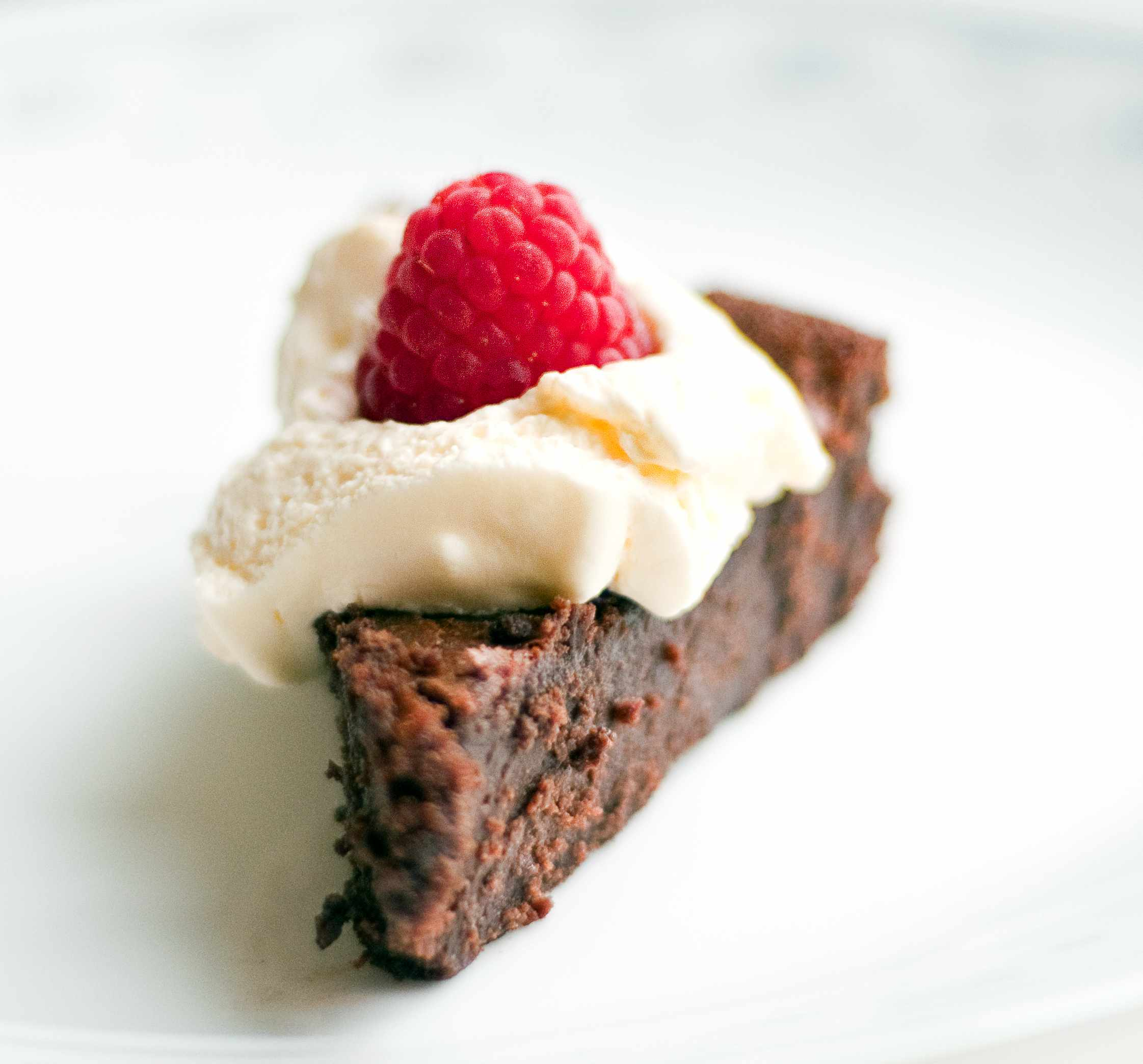 Gluten free flour-less chocolate cake with a raspberry on top