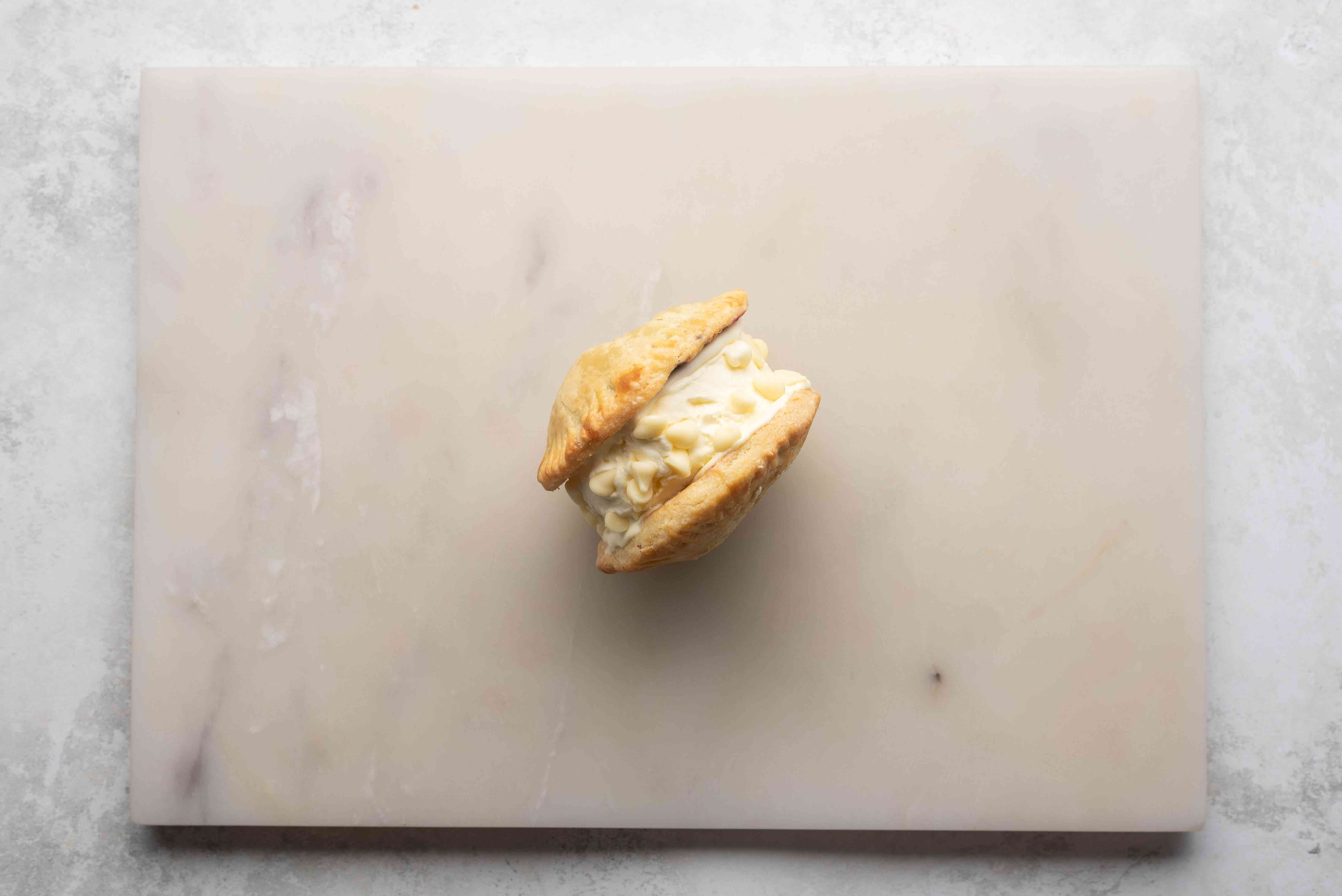 Mini Pie Ice Cream Sandwich with white chocolate chips on the sides, on a cutting board