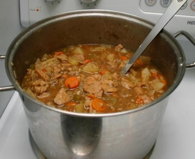 A big pot of seitan and beer stew cooking on a stovetop