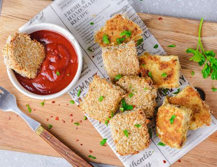Breaded tofu nuggets on a cutting board with dipping sauce