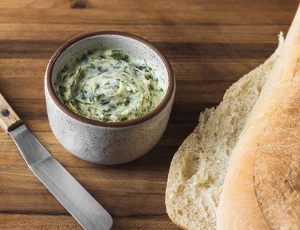 Simple garlic butter recipe in a crock with bread alongside