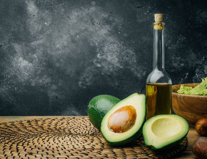 Avocado and avocado oil on a wooden background