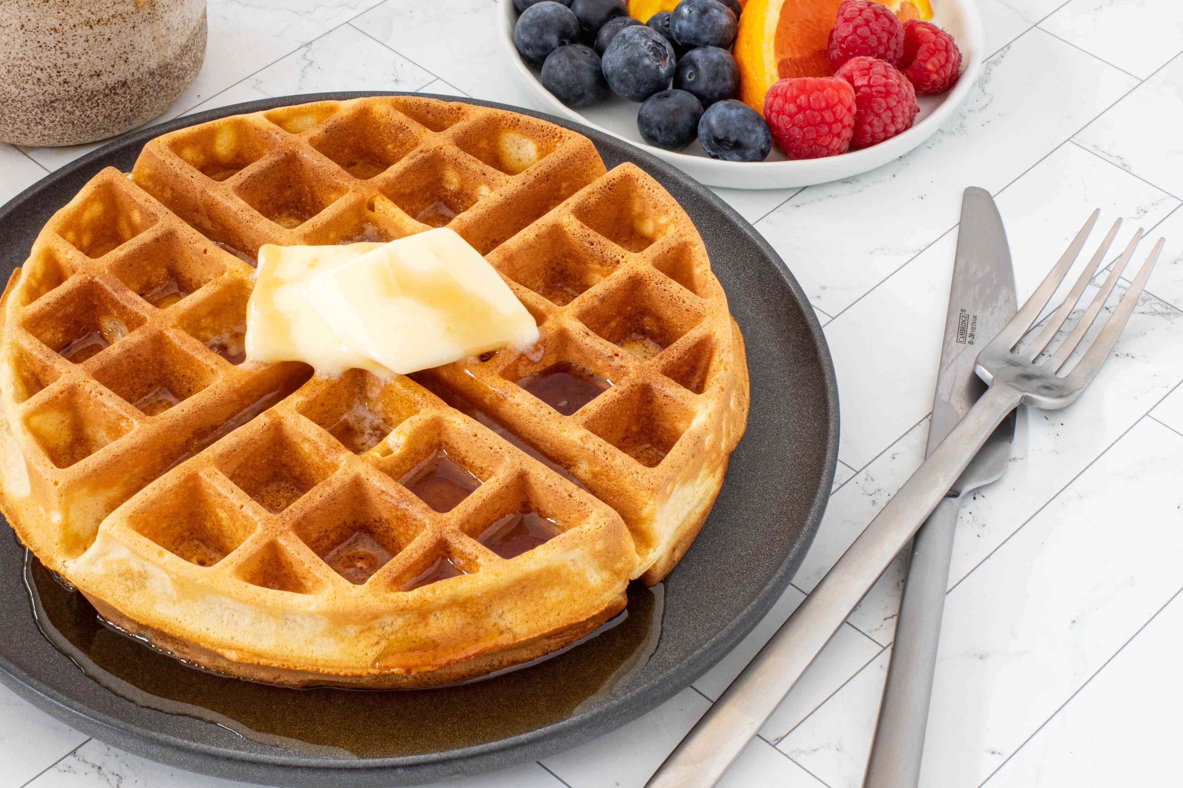 waffle with butter and syrup with fruit and berries on the side