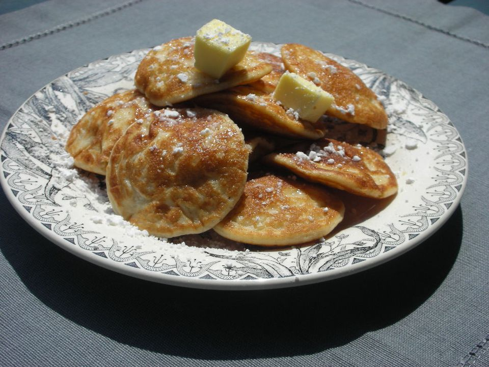 Poffertjes on a plate with butter and powdered sugar