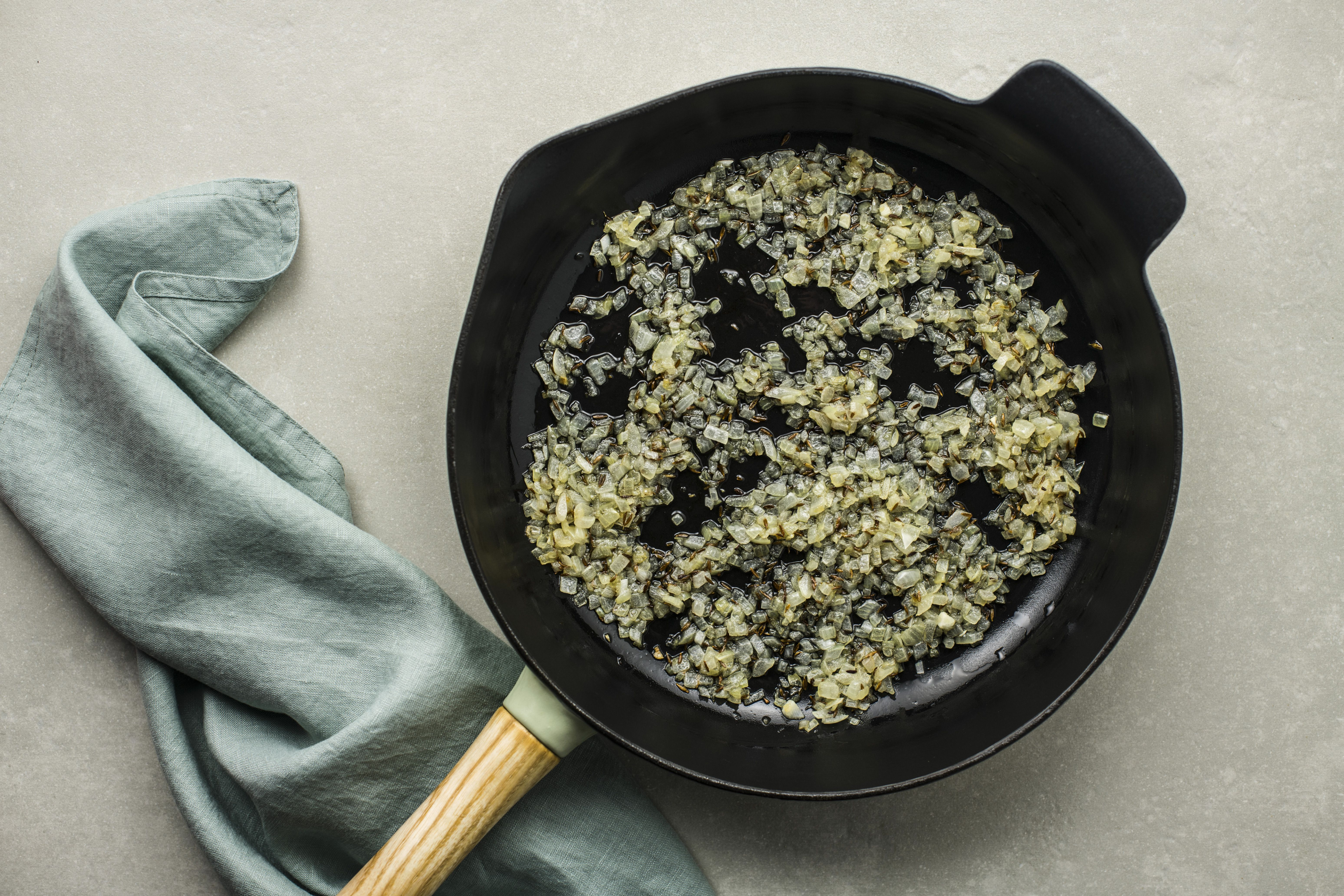Onions and cumin seeds in frying pan