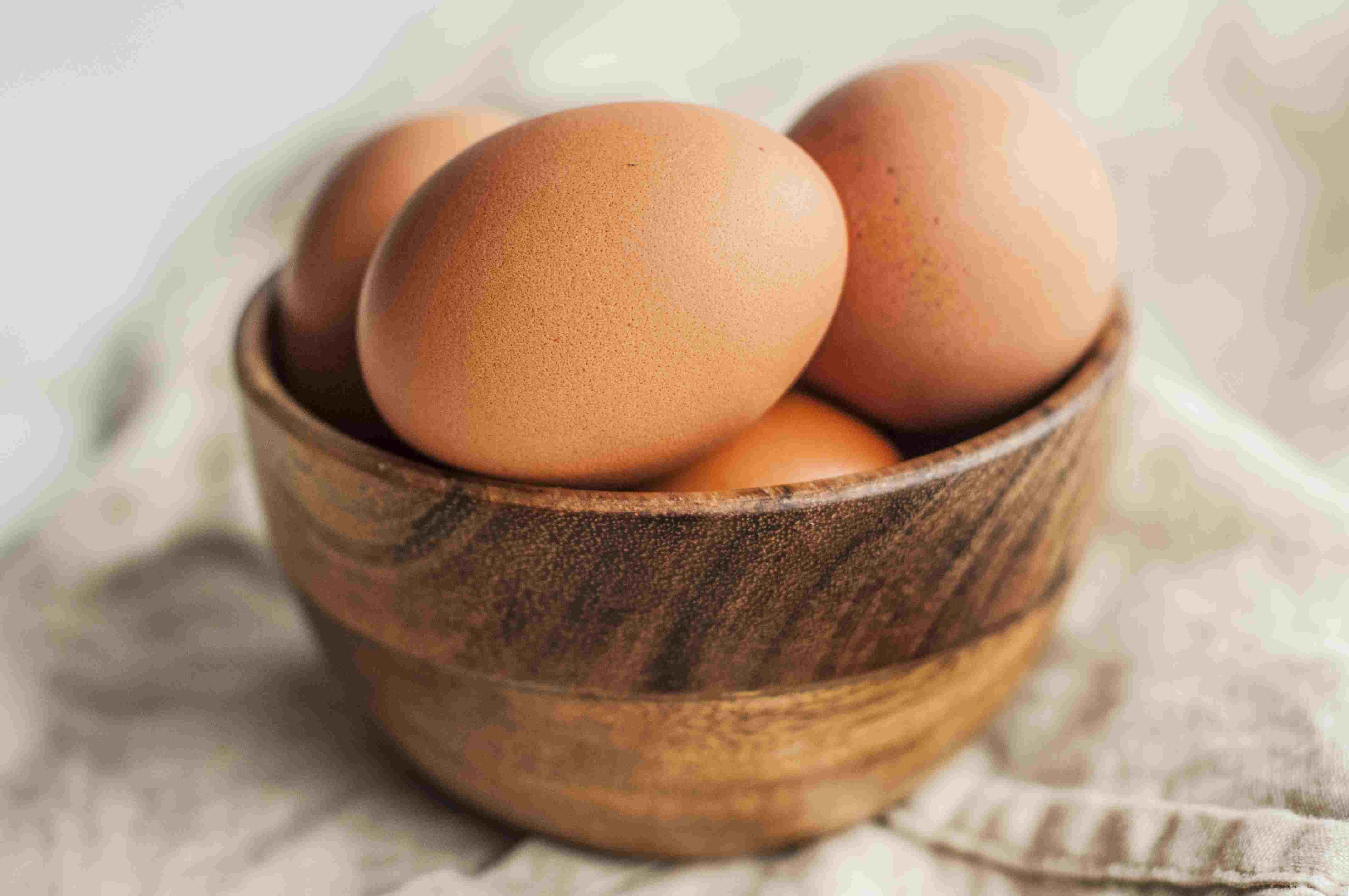 Finished hard-boiled eggs in a wooden bowl