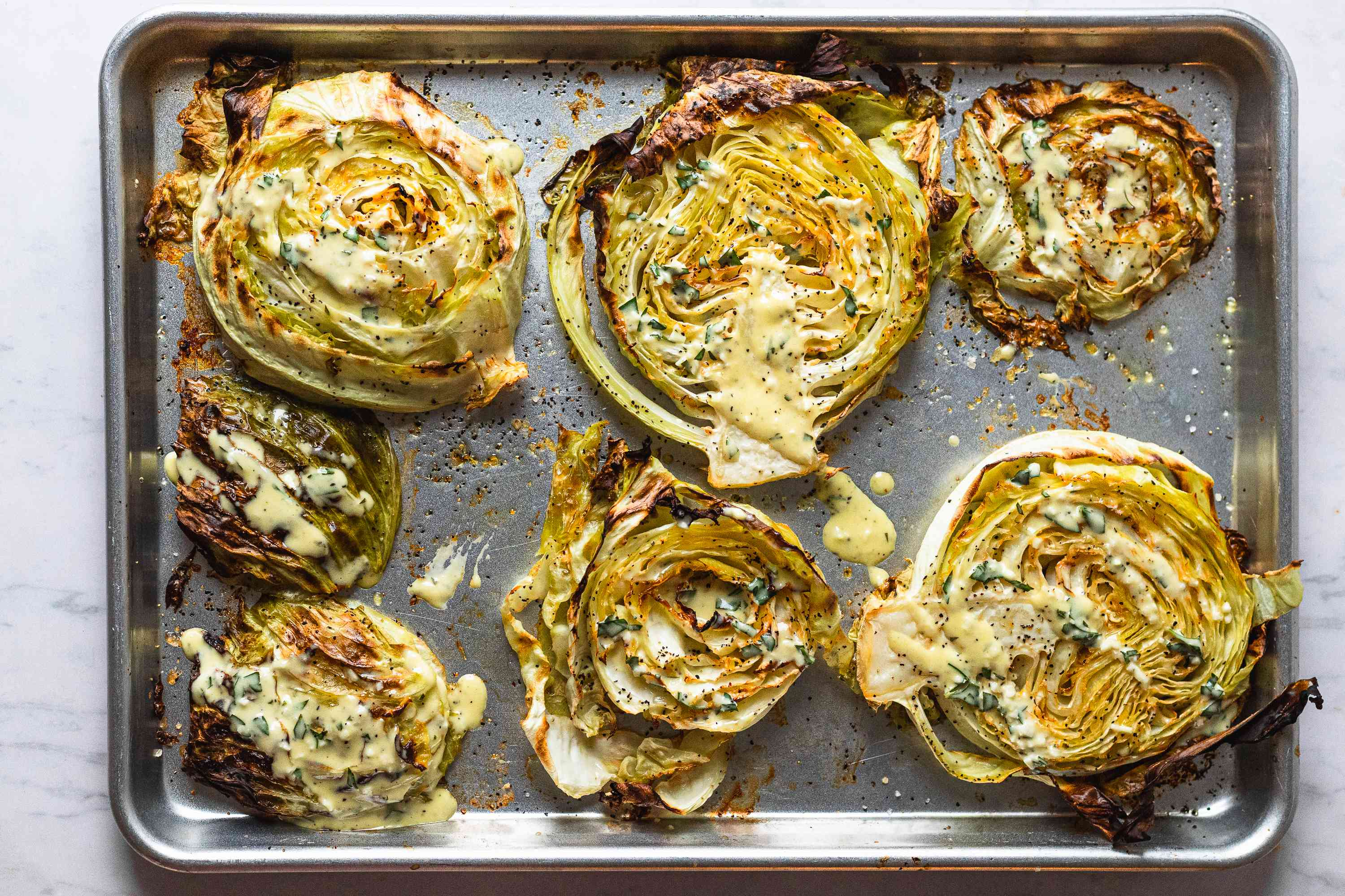 Baked Cabbage Steaks with dressing on a baking sheet