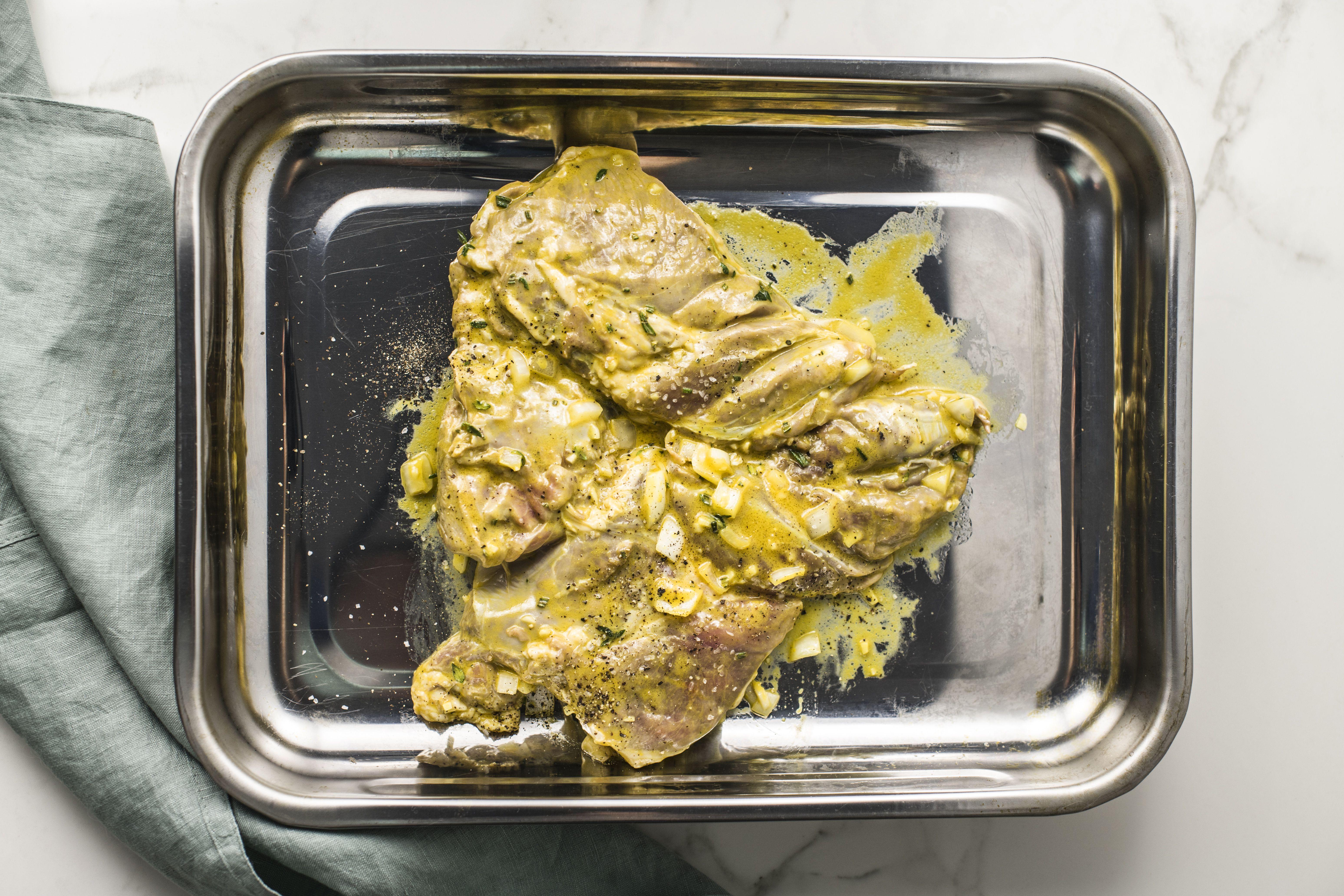 Lamb in metal baking pan seasoned with salt and pepper