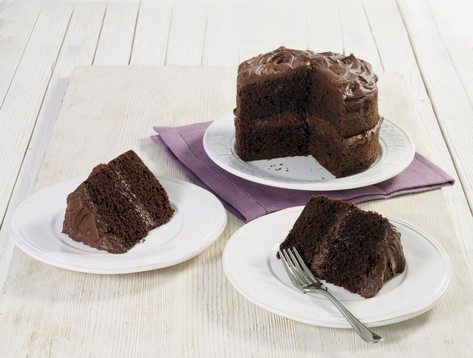 Chocolate cake and two pieces on white plates on a white surface