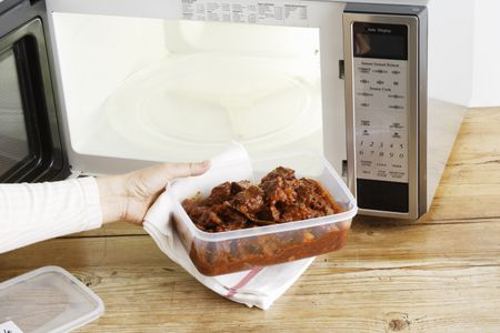 Woman Heating Leftovers In Microwave