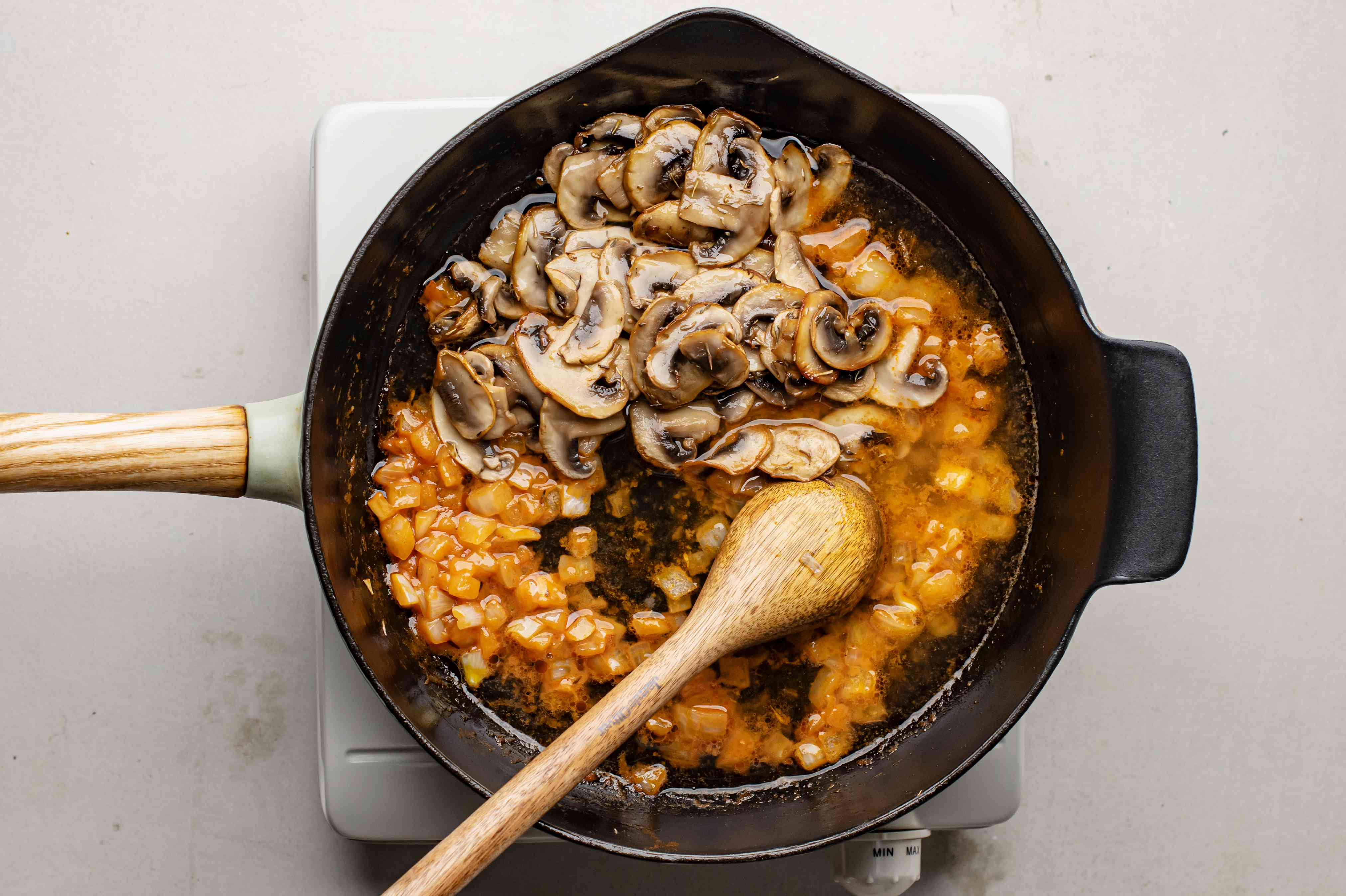 Mushrooms, onions, and tomato paste cooking in skillet
