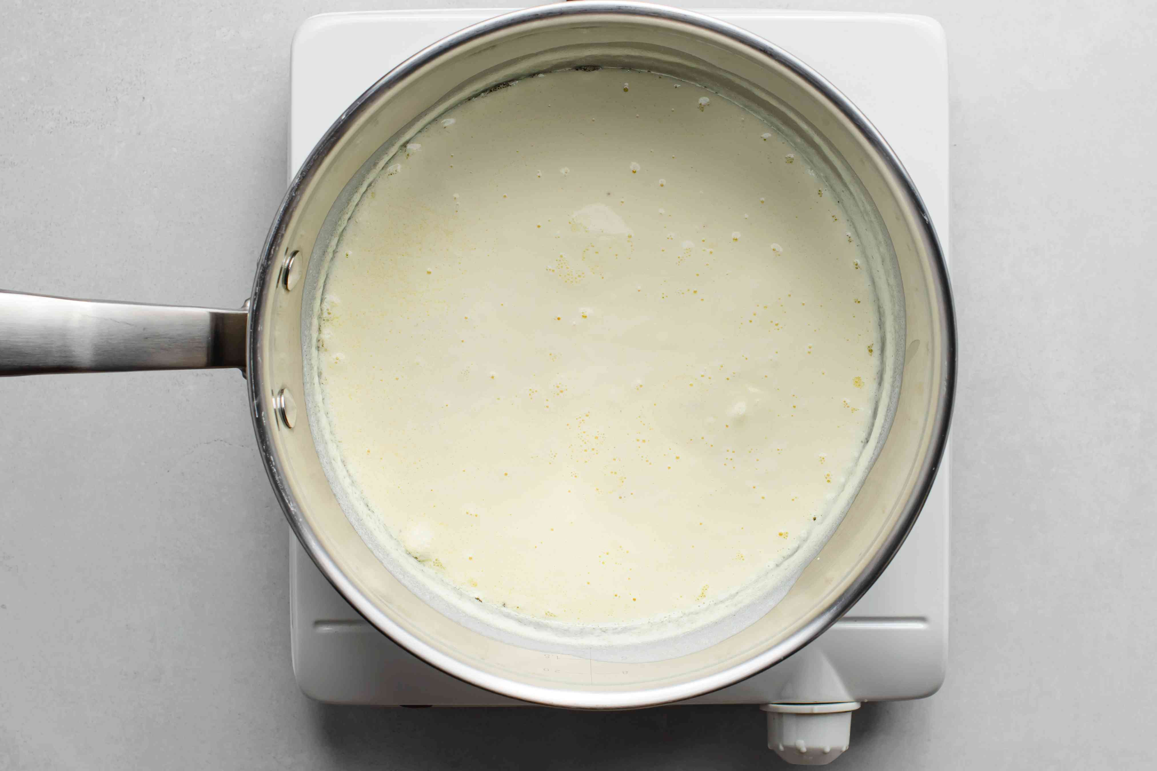 Alfredo sauce and milk in a pot