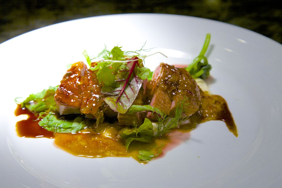 A plate of sliced duck breast with gastrique