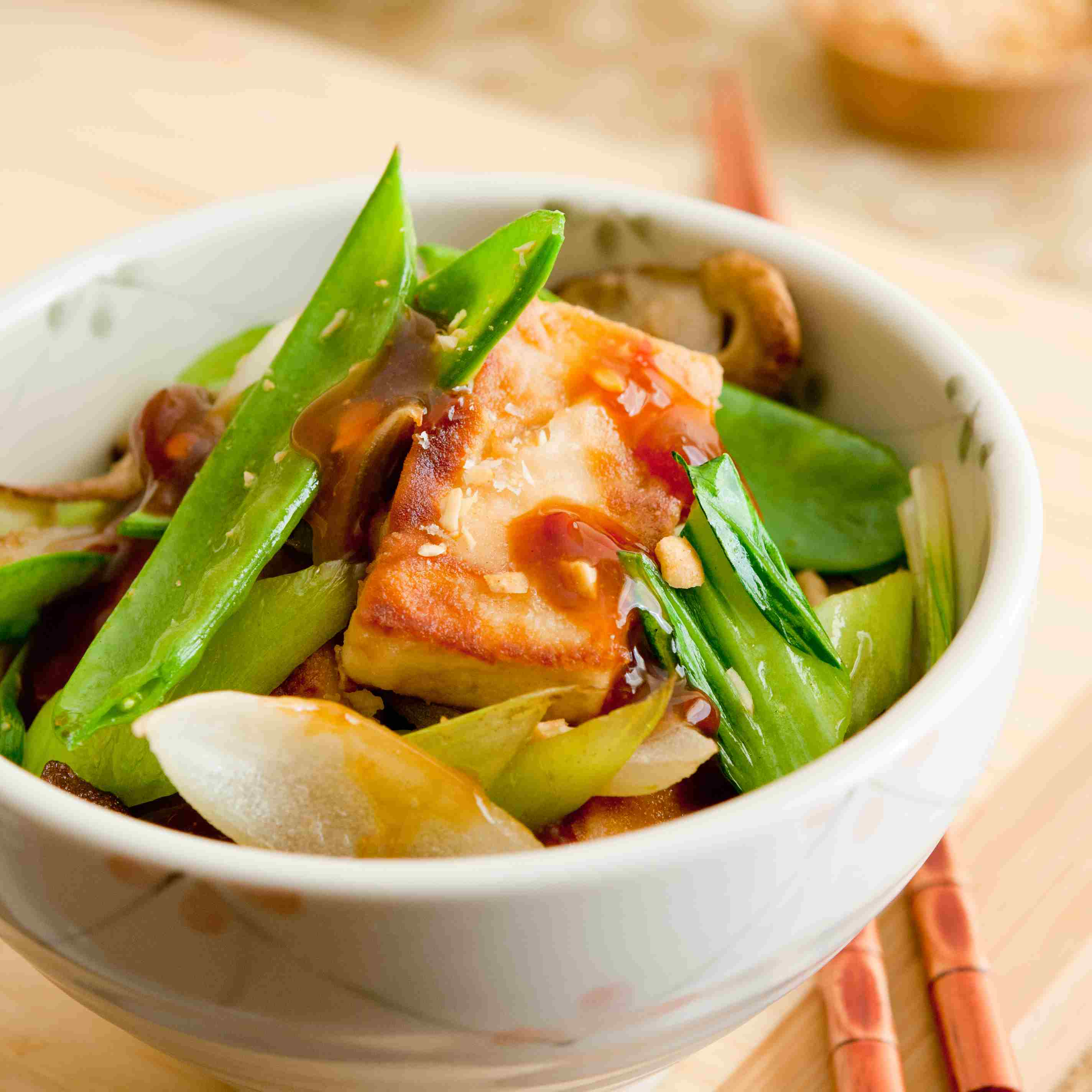 Vegetable stir-fry with tofu in a bowl along with chopsticks