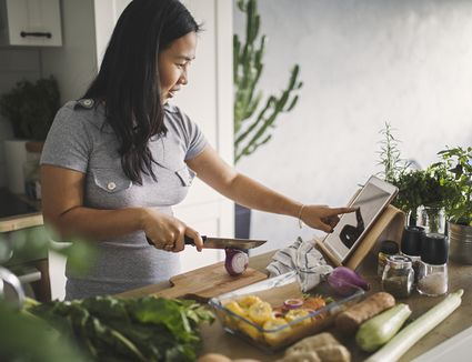 Woman Using iPad to Cook