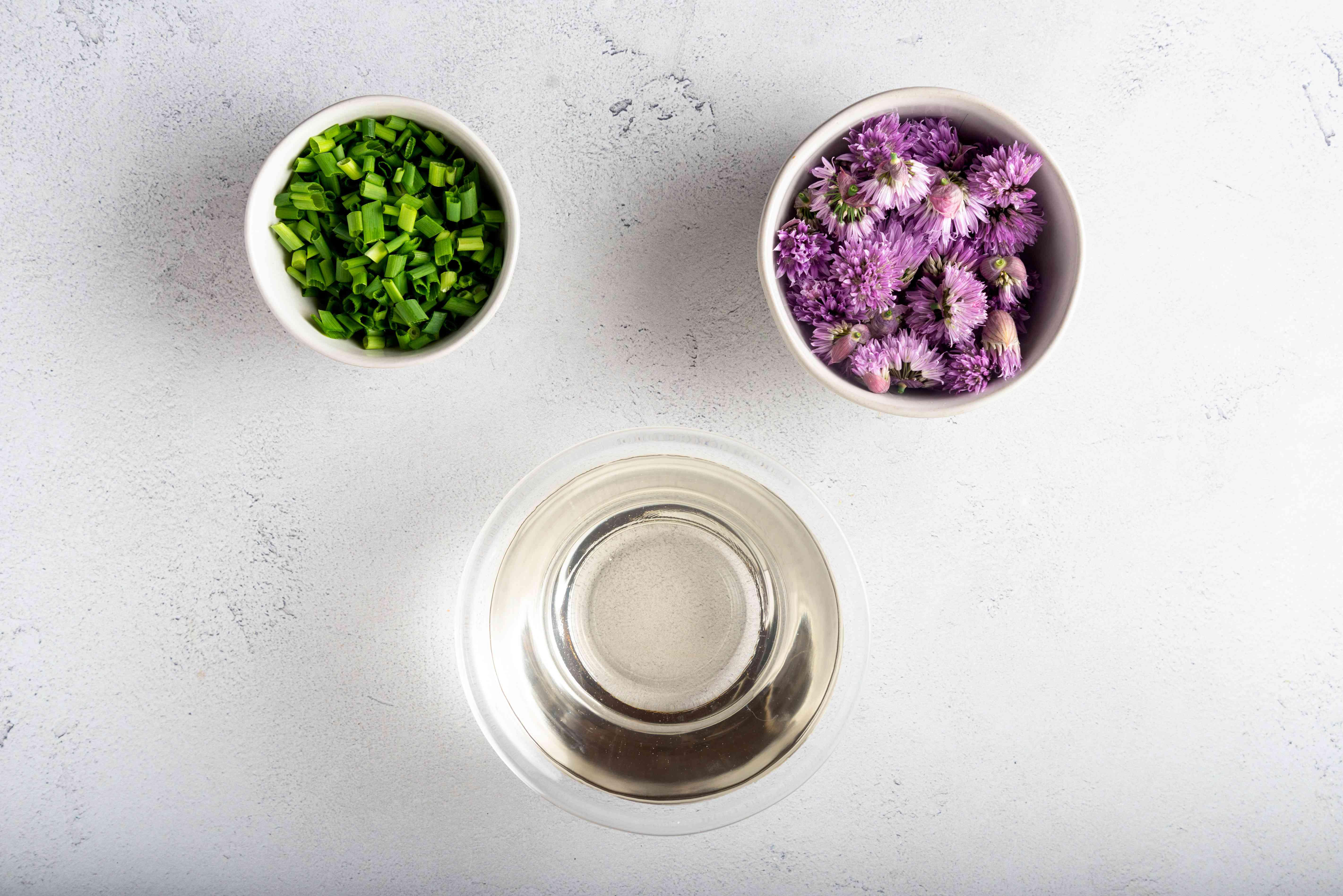 chive blossoms, vinegar and chopped chives in bowls