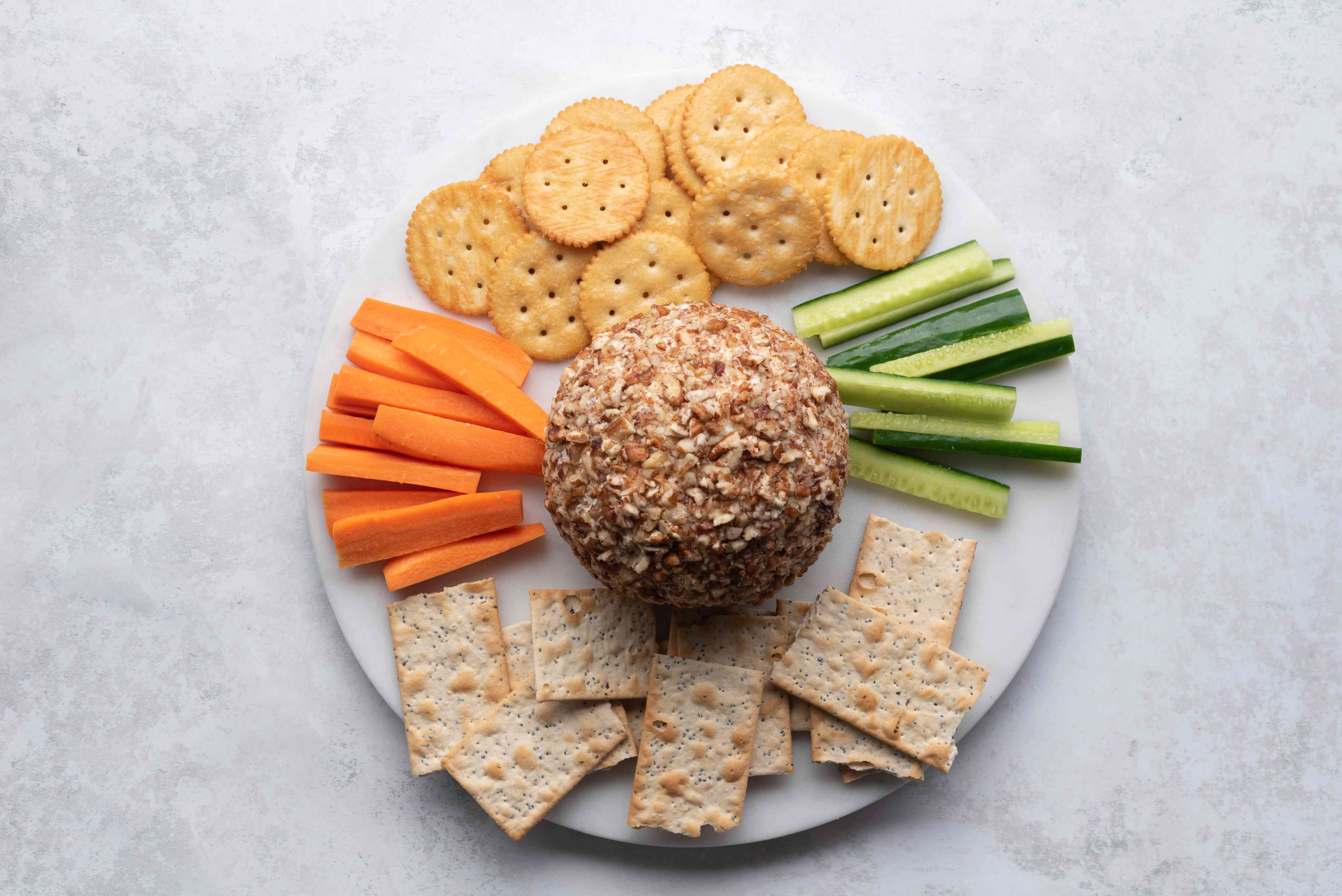 Festive Party Cheese Ball With Pecans, served with crackers and vegetables