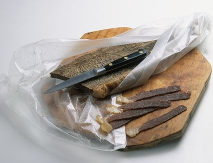 Cured and dried beef Biltong on chopping board, with some slices cut away, wrapped in plastic, close
