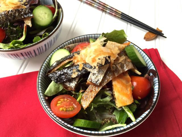 A bowl of mixed baby greens with grilled salmon skin and citrus soy dressing