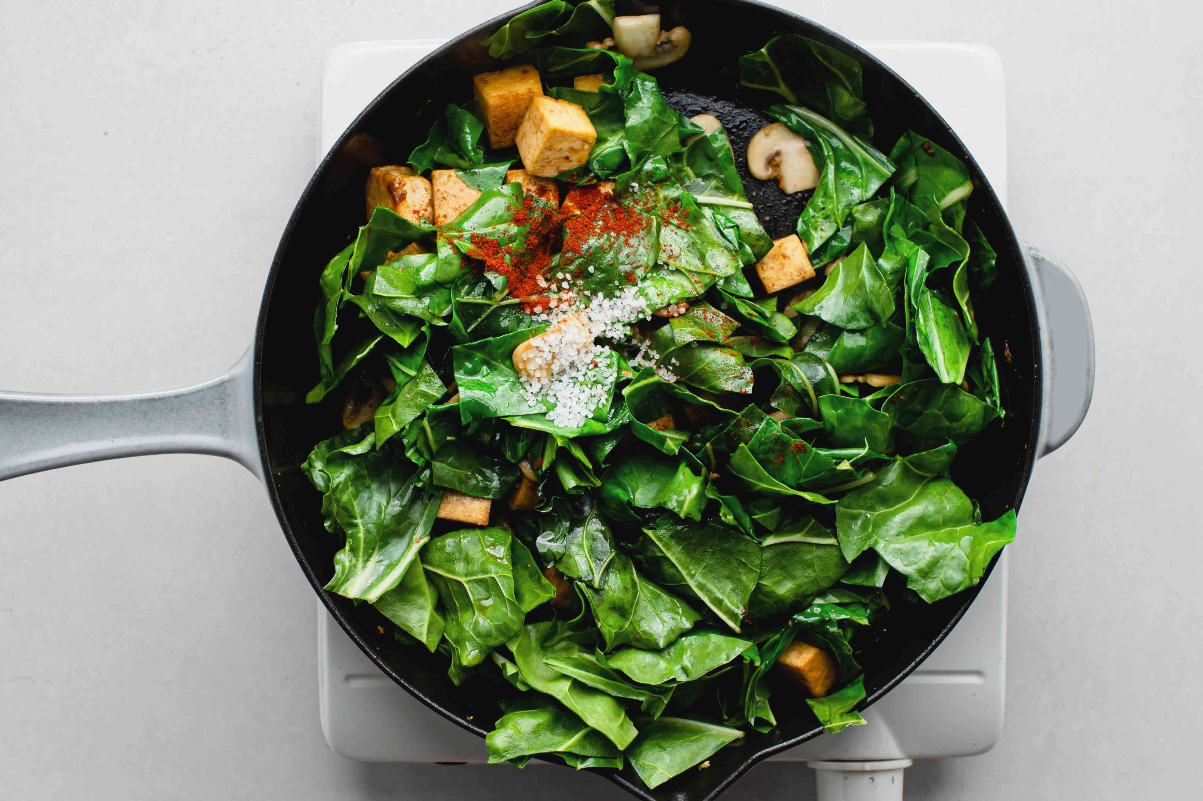 salt and cayenne pepper added to Swiss Chard and tofu in the skillet